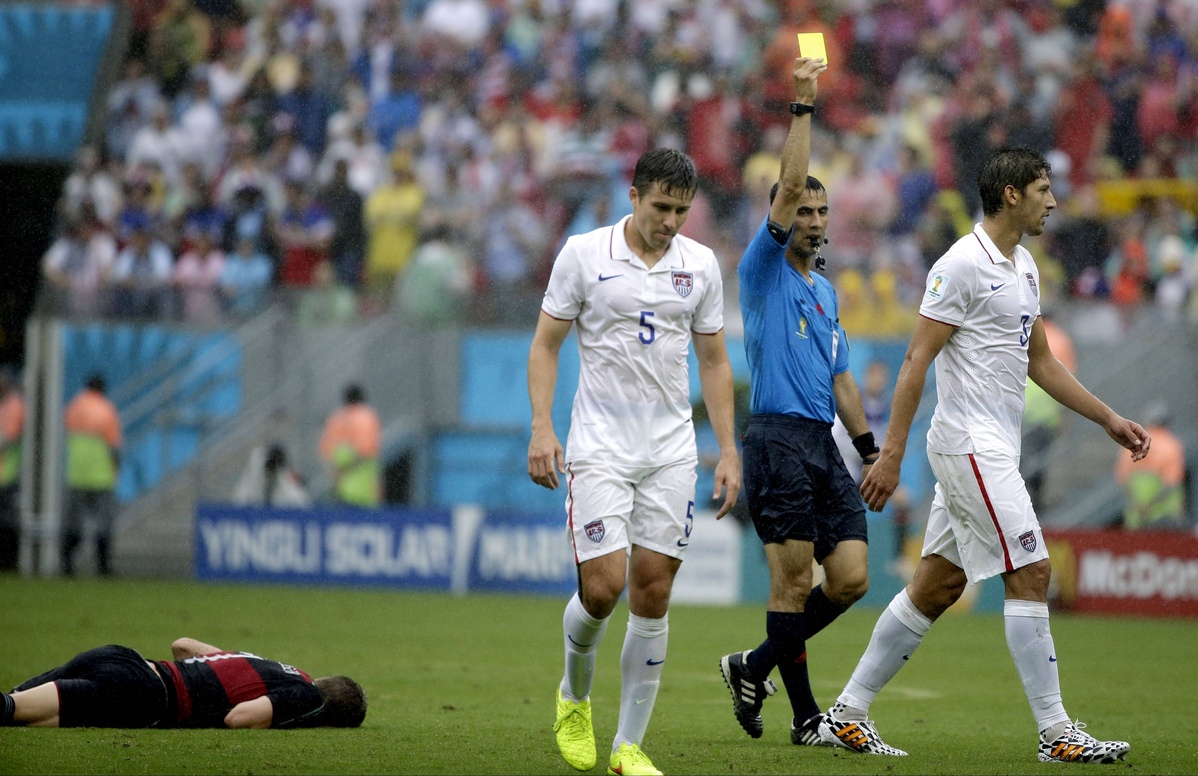 United States' Omar Gonzalez is given a yellow card by referee Ravshan Irmatov from Uzbekistan after an incident involving Germany's Bastian Schweinsteiger, left, during the group G World Cup soccer match between the USA and Germany at the Arena Pernambuco in Recife, Brazil, Thursday, June 26, 2014. At center is United States' Matt Besler.