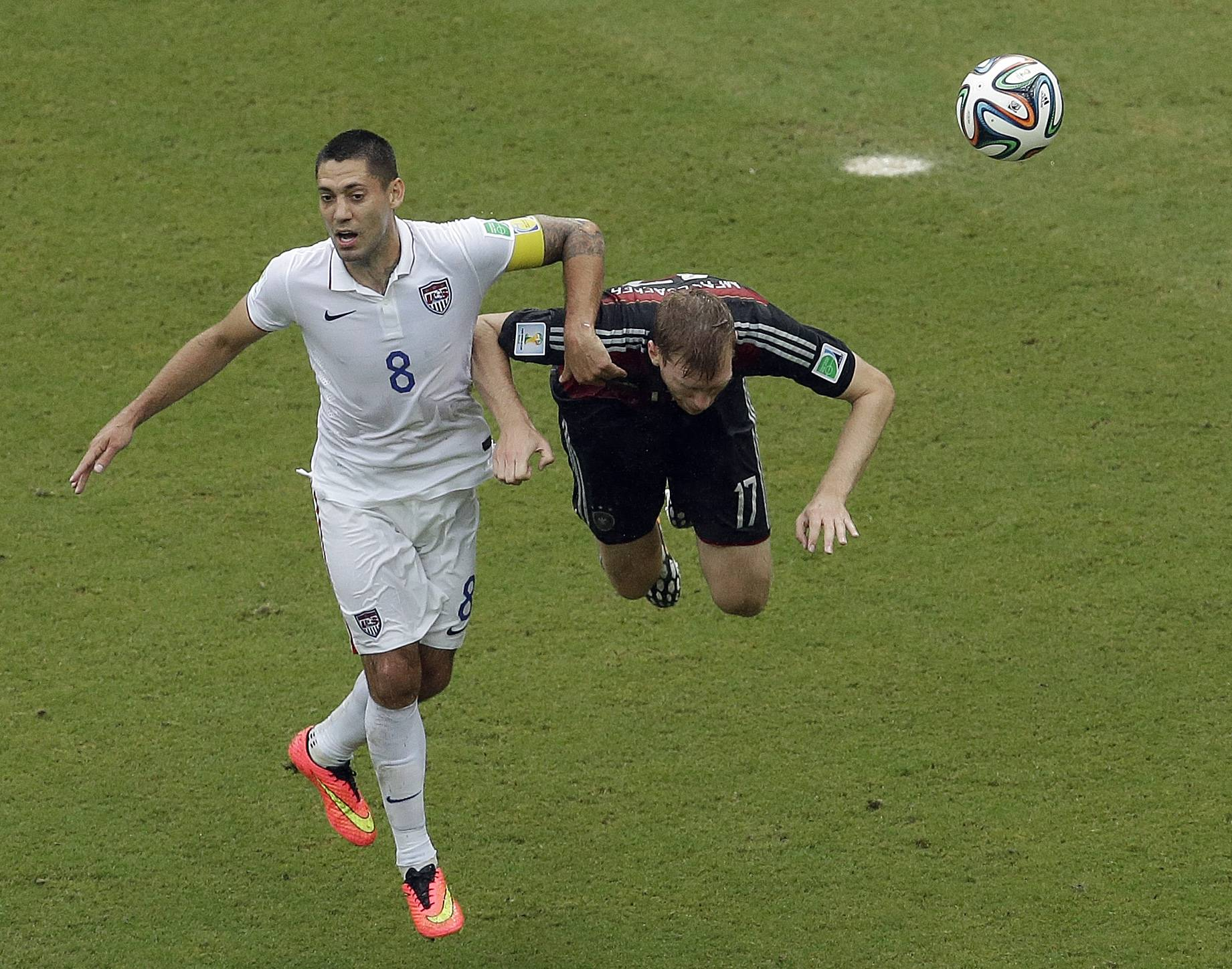 United States' Clint Dempsey (8) and Germany's Per Mertesacker battle for the ball during the group G World Cup soccer match between the USA and Germany at the Arena Pernambuco in Recife, Brazil, Thursday, June 26, 2014.
