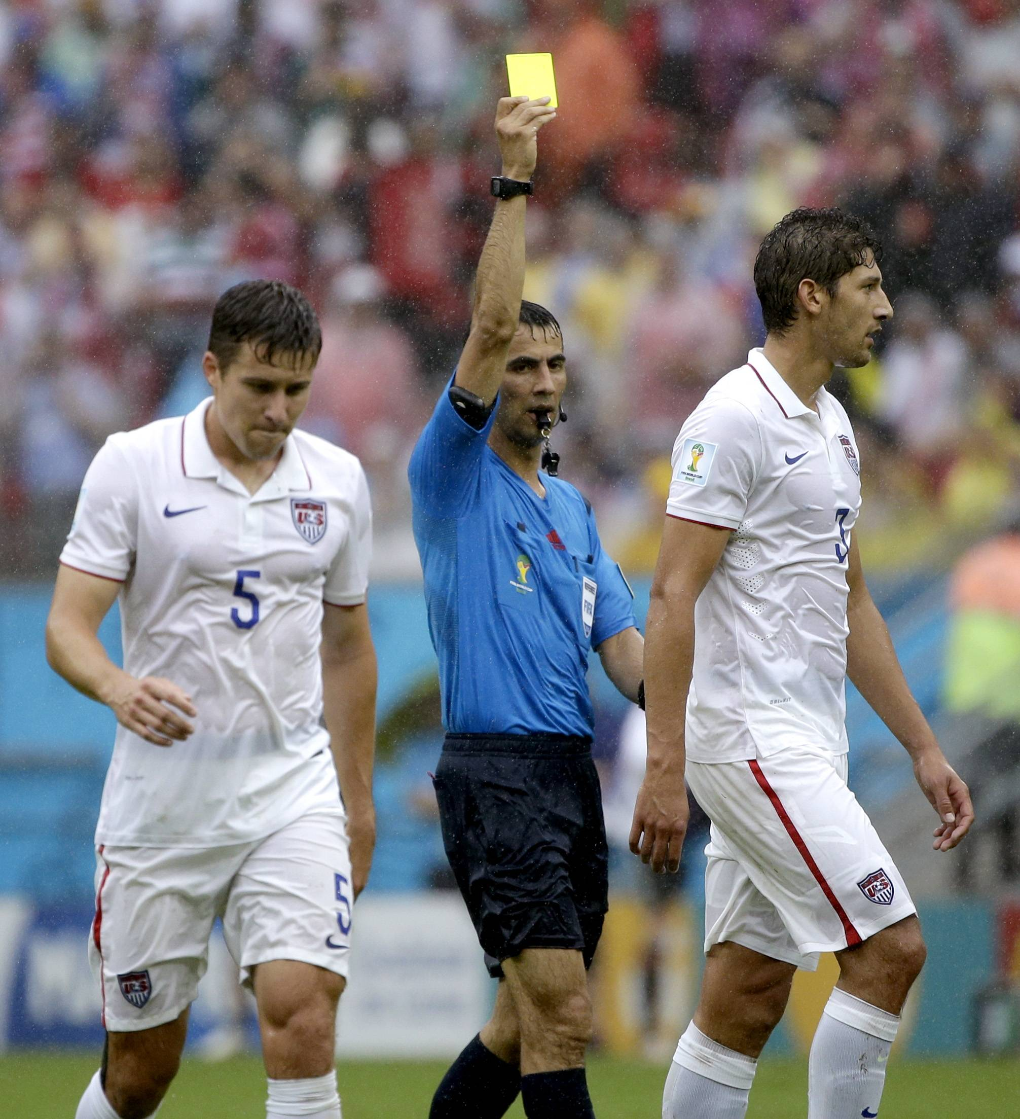 United States' Omar Gonzalez walks away with teammate Matt Besler (5) as referee Ravshan Irmatov from Uzbekistan gives Gonzalez a yellow card during the group G World Cup soccer match between the USA and Germany at the Arena Pernambuco in Recife, Brazil, Thursday, June 26, 2014.