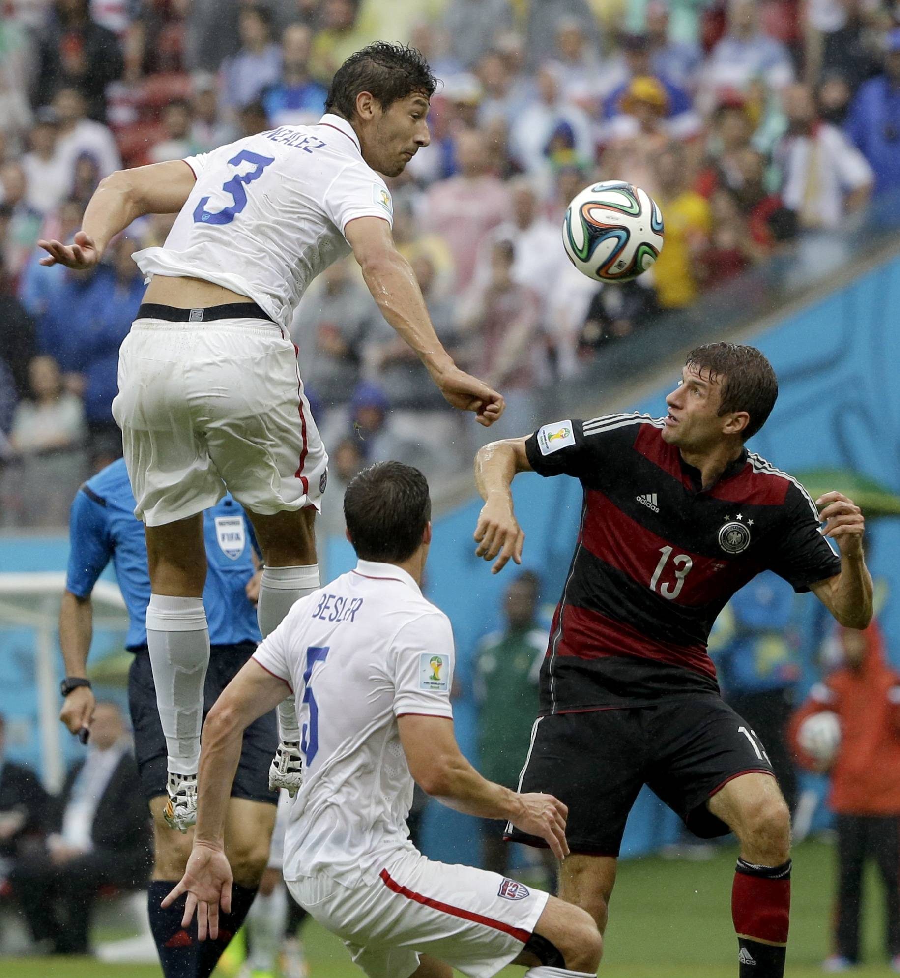 United States' Omar Gonzalez goes over Germany's Thomas Mueller to head the ball as United States' Matt Besler looks on during the group G World Cup soccer match between the USA and Germany at the Arena Pernambuco in Recife, Brazil, Thursday, June 26, 2014.