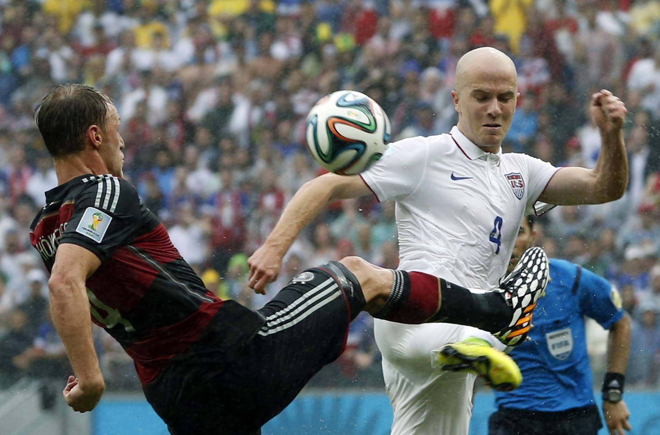 Germany's Benedikt Hoewedes, left, and United States' Michael Bradley challenge for the ball during the group G World Cup soccer match between the USA and Germany at the Arena Pernambuco in Recife, Brazil, Thursday, June 26, 2014.