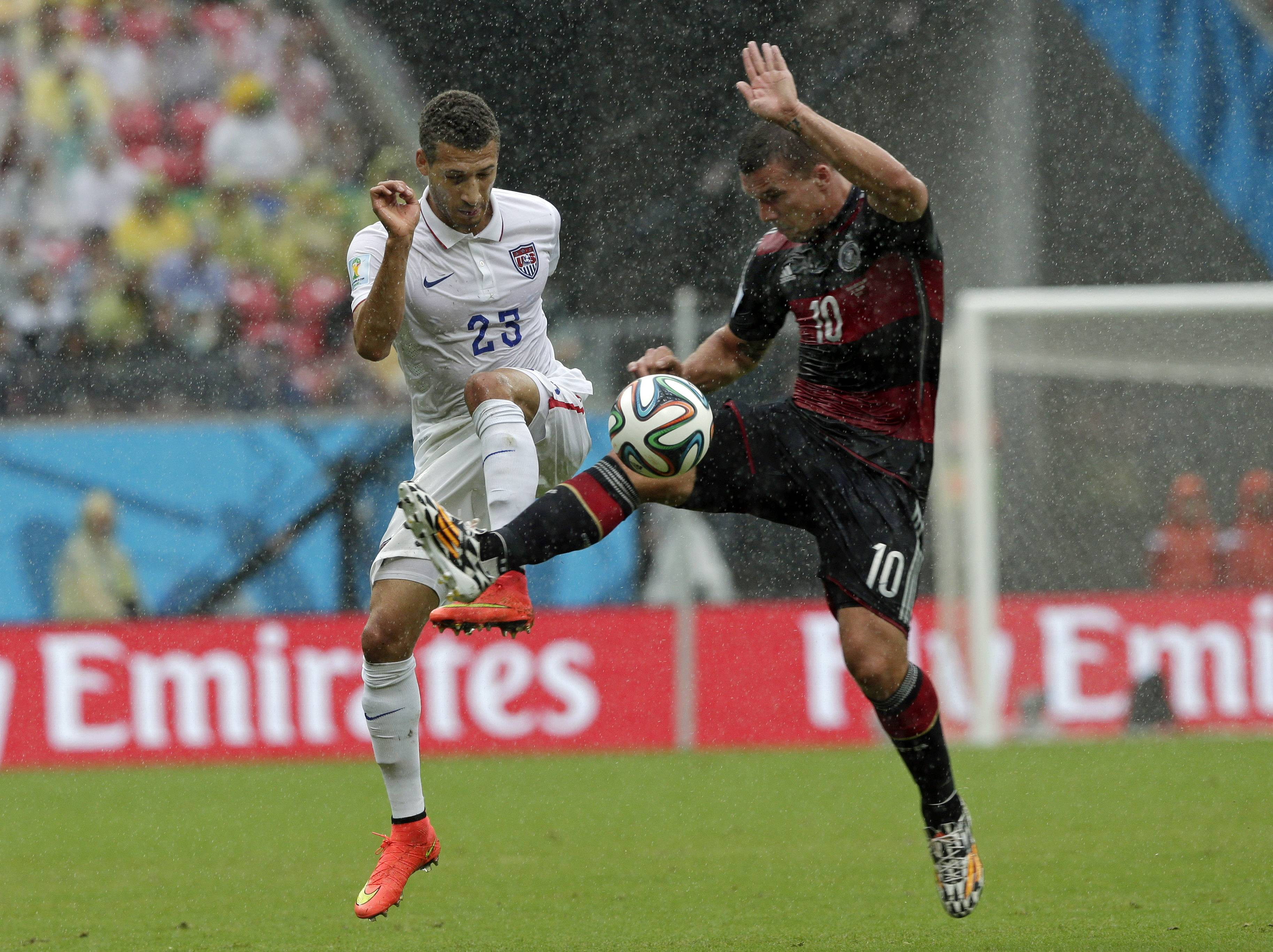 United States' Fabian Johnson, left, and Germany's Lukas Podolski challenge for the ball during the group G World Cup soccer match between the USA and Germany at the Arena Pernambuco in Recife, Brazil, Thursday, June 26, 2014.