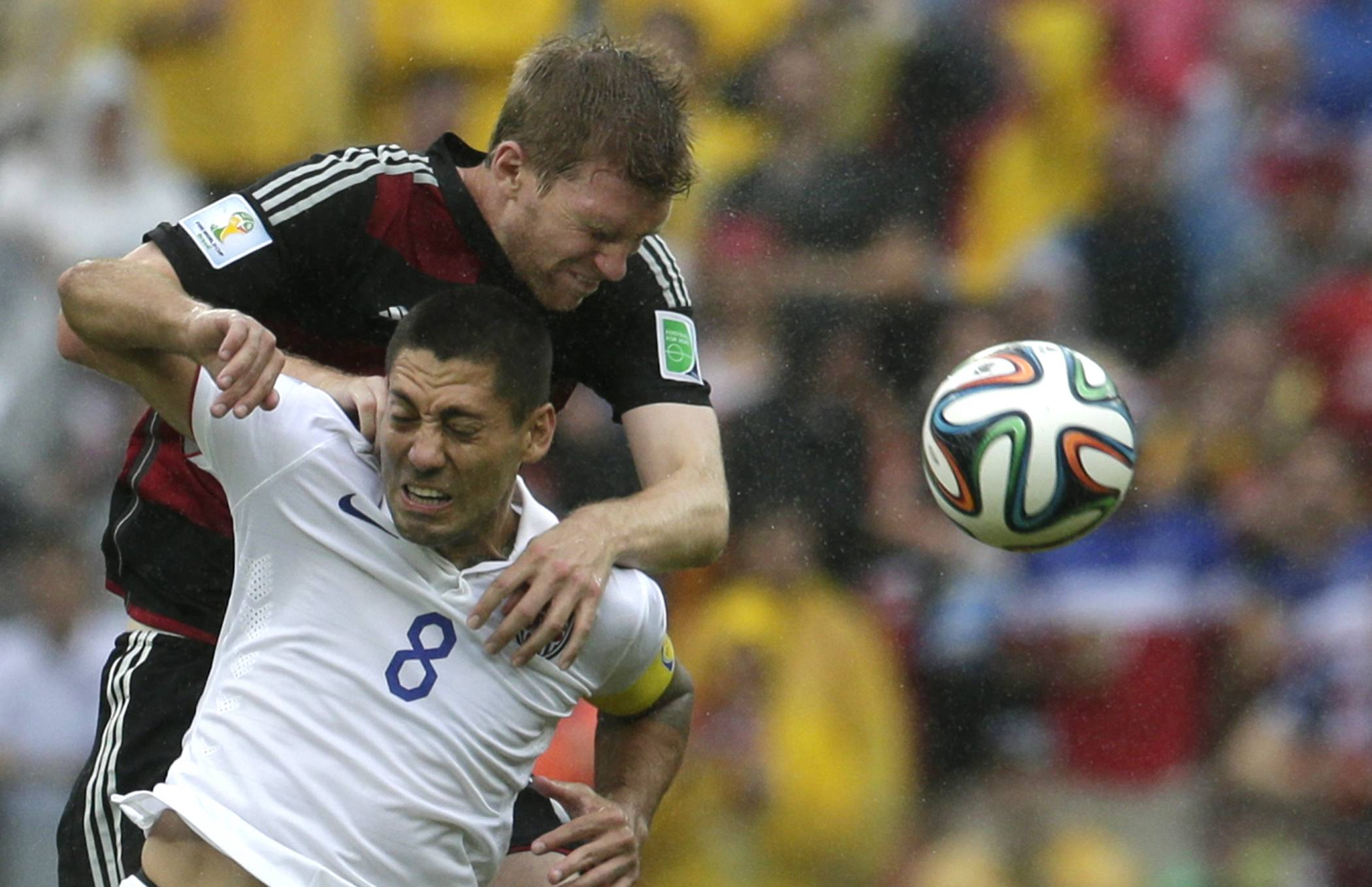 Germany's Per Mertesacker, back, and United States' Clint Dempsey go for a header during the group G World Cup soccer match between the USA and Germany at the Arena Pernambuco in Recife, Brazil, Thursday, June 26, 2014.