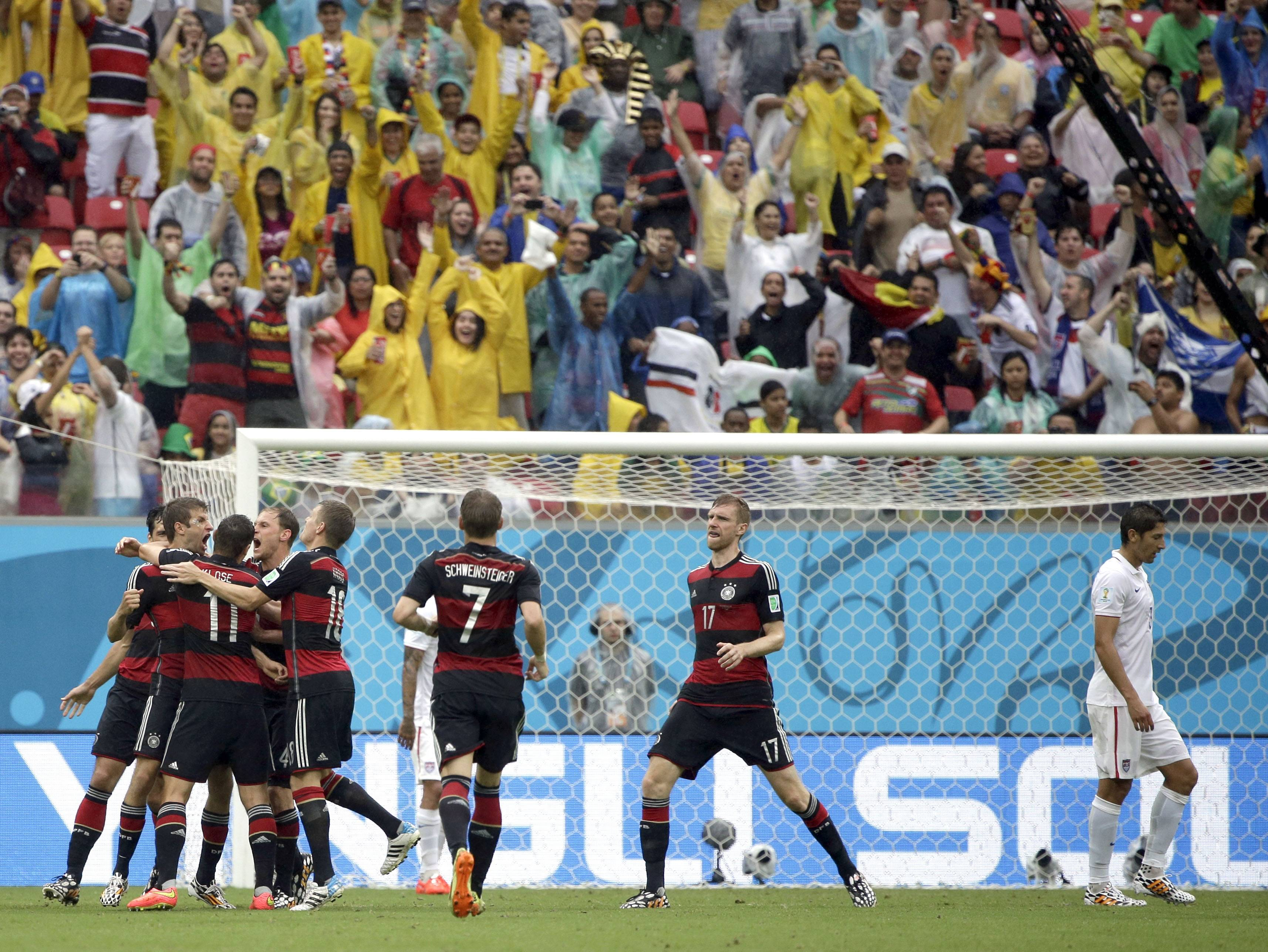 Germany's Thomas Mueller, left, celebrates with his teammates after scoring his side's first goal during the group G World Cup soccer match between the United States and Germany at the Arena Pernambuco in Recife, Brazil, Thursday, June 26, 2014.