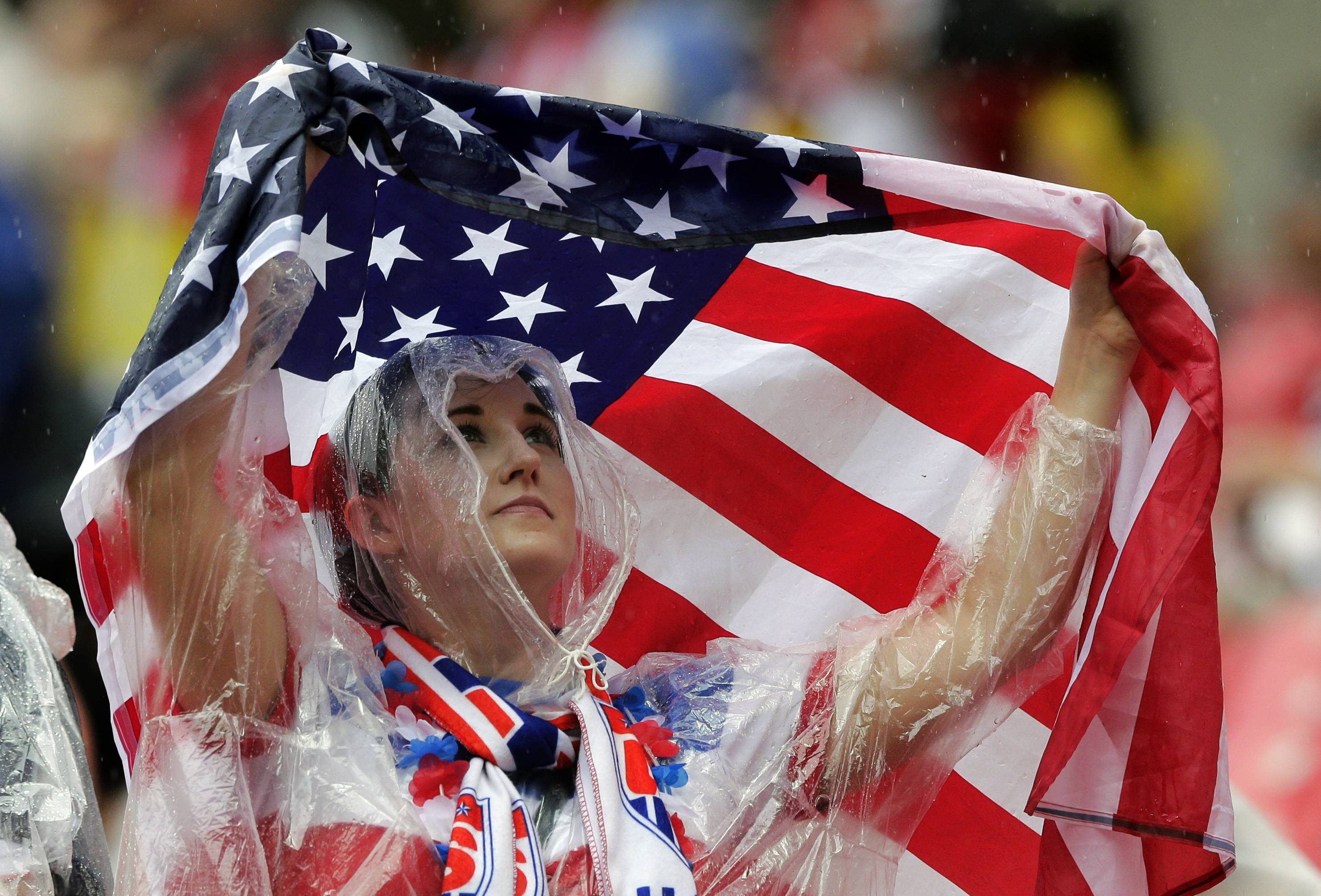 A US supporter uses an American flag to protect herself against the rain during the group G World Cup soccer match between the USA and Germany at the Arena Pernambuco in Recife, Brazil, Thursday, June 26, 2014.