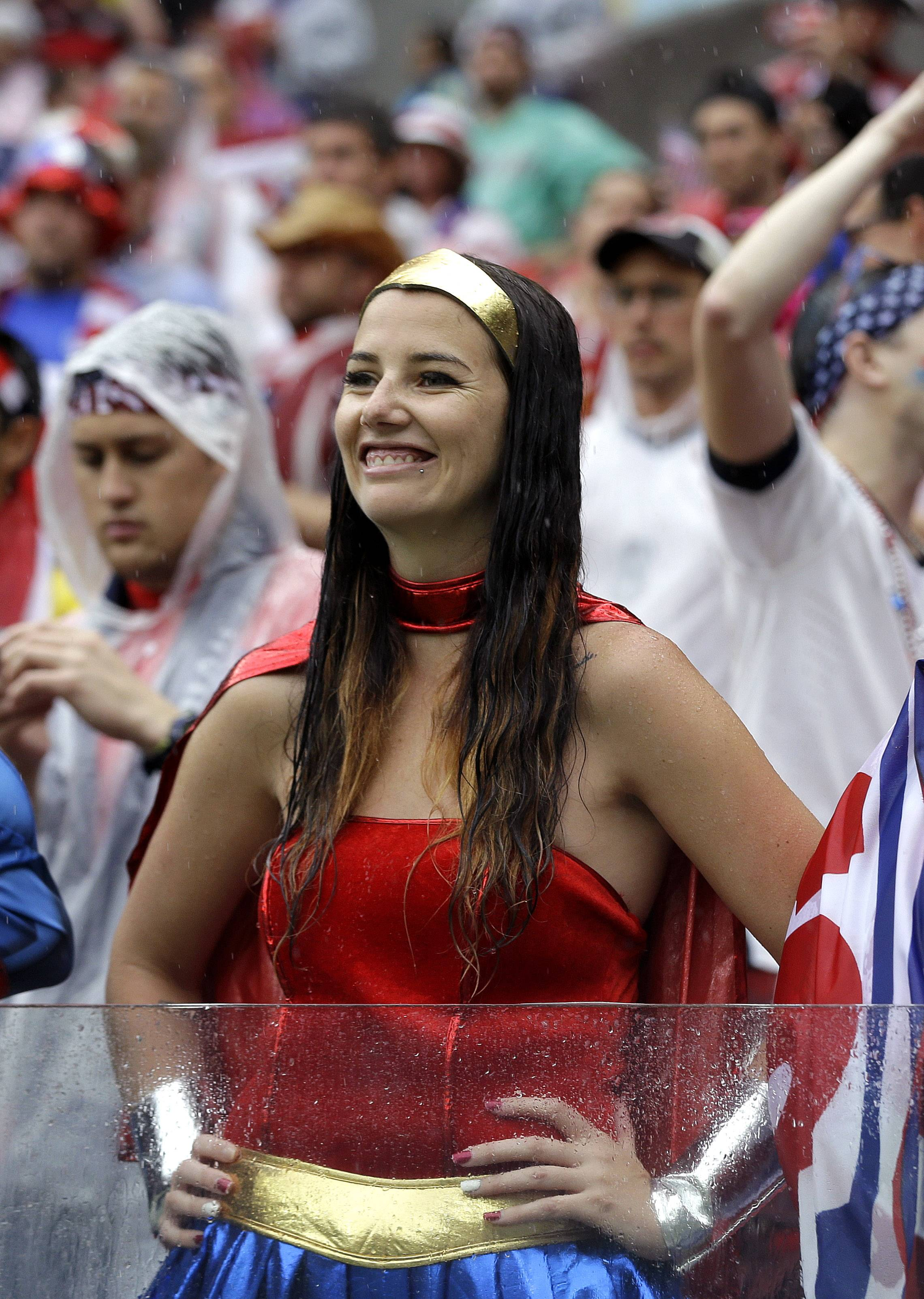 "A USA supporter, dressed as ""Wonder Woman"" waits in the rain for the group G World Cup soccer match between the United States and Germany at the Arena Pernambuco in Recife, Brazil, Thursday, June 26, 2014."