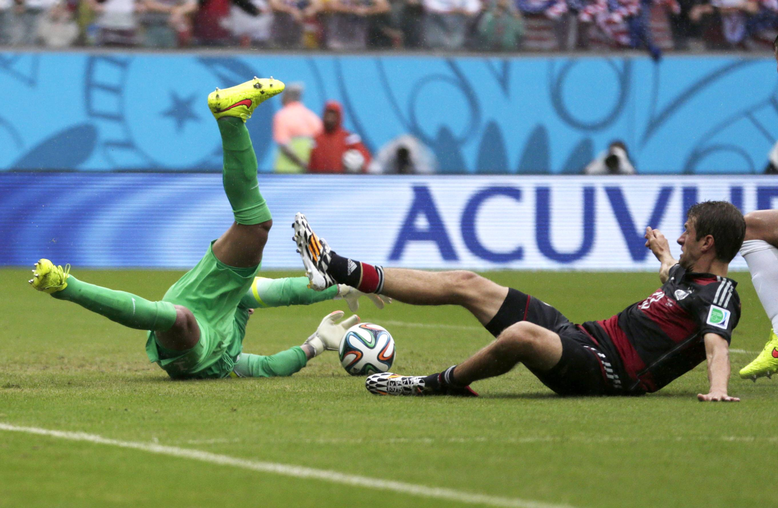 United States' goalkeeper Tim Howard goes down to make a save on Germany's Thomas Mueller during the group G World Cup soccer match between the United States and Germany at the Arena Pernambuco in Recife, Brazil, Thursday, June 26, 2014.