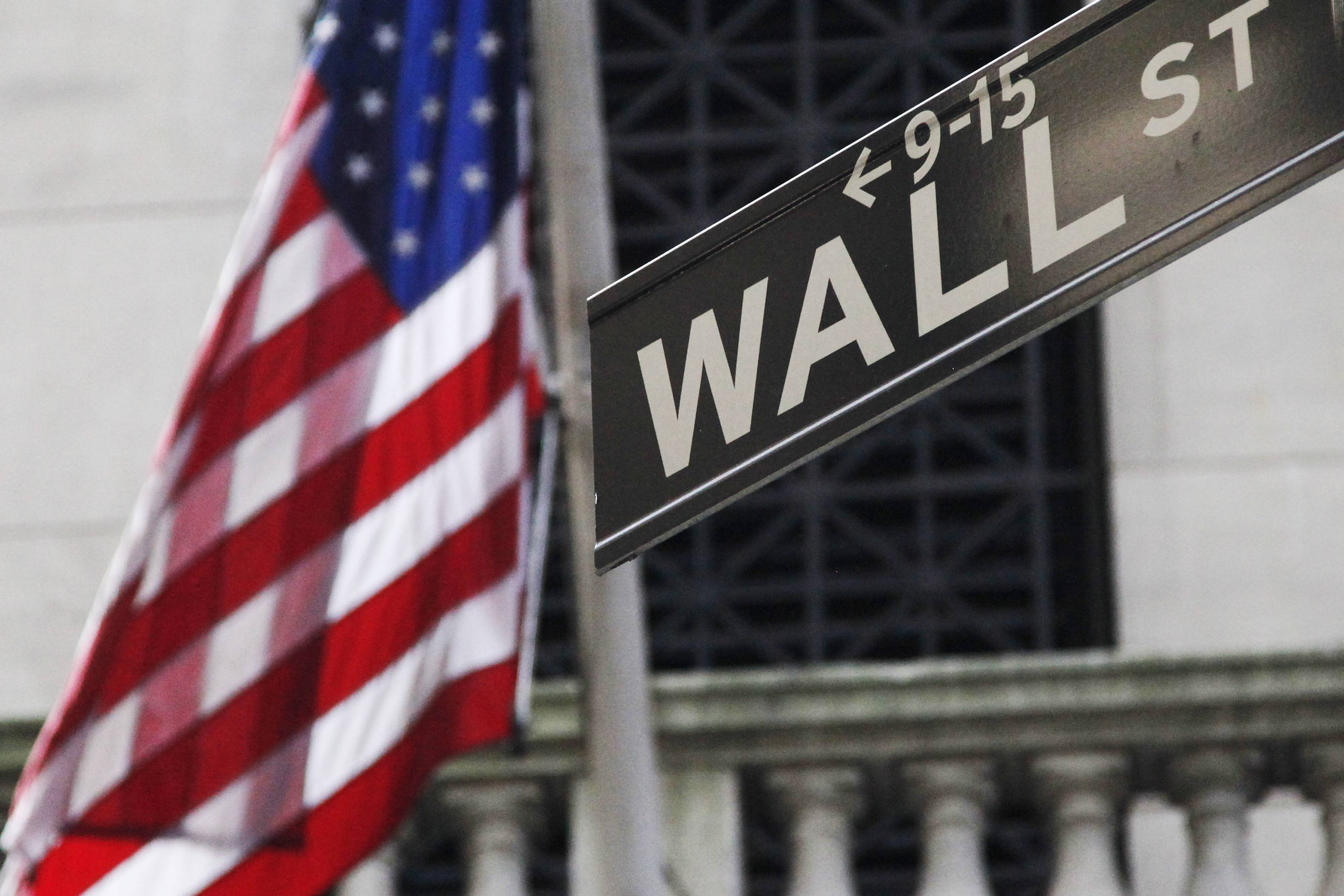 The American flag and Wall St. street sign outside the New York Stock Exchange, in New York.