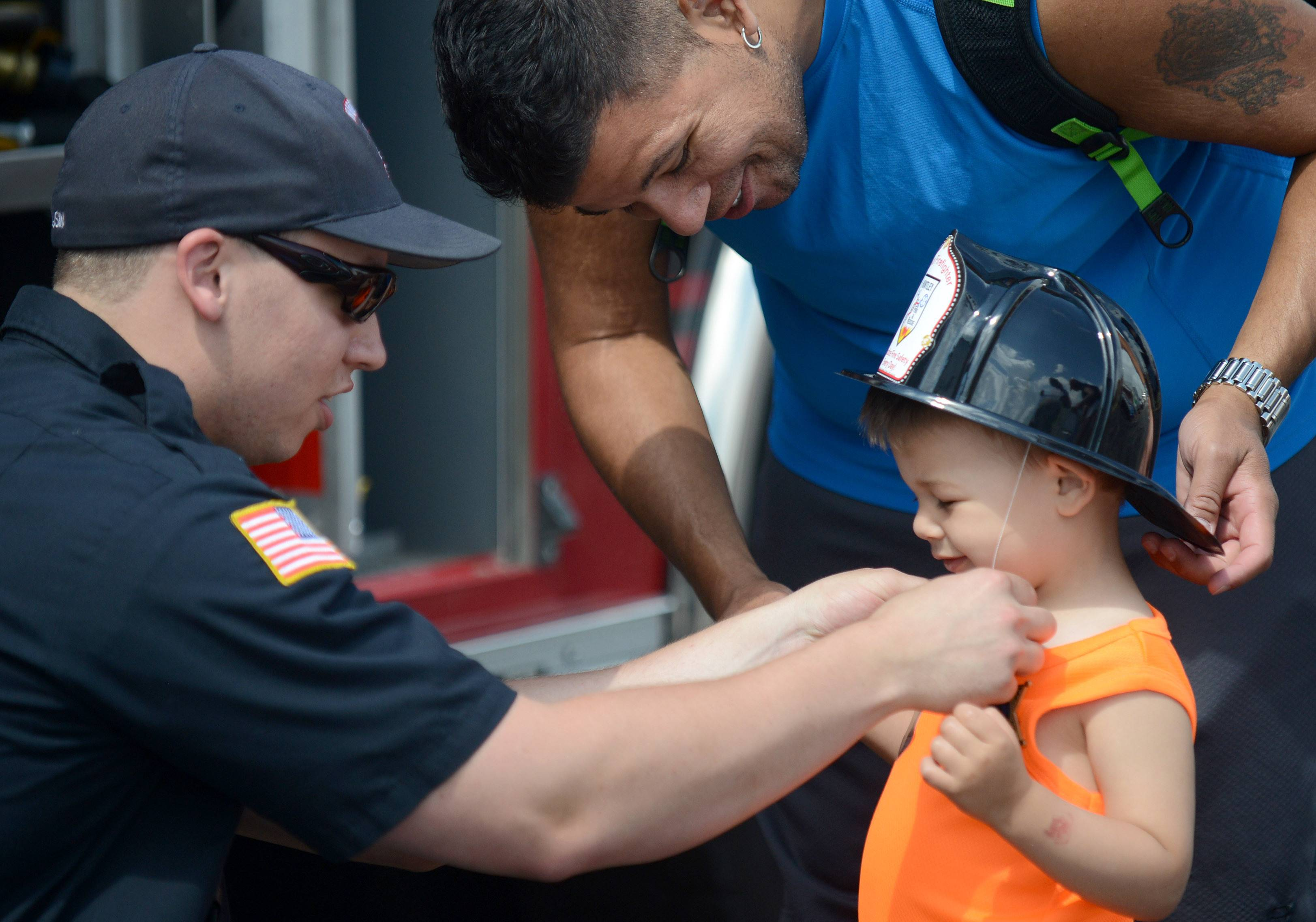 Huntley firefighter/paramedic Eric Slusin dons Ricky Magana Jr., 2, of Lake in the Hills with a fireman's helmet as his dad, Rick, helps out. Ricky led his father around the Touch-a-Truck display at the Children's Safety Expo in Algonquin. Ricky is a big fan of all kinds of cars and trucks, especially construction trucks, said his father.