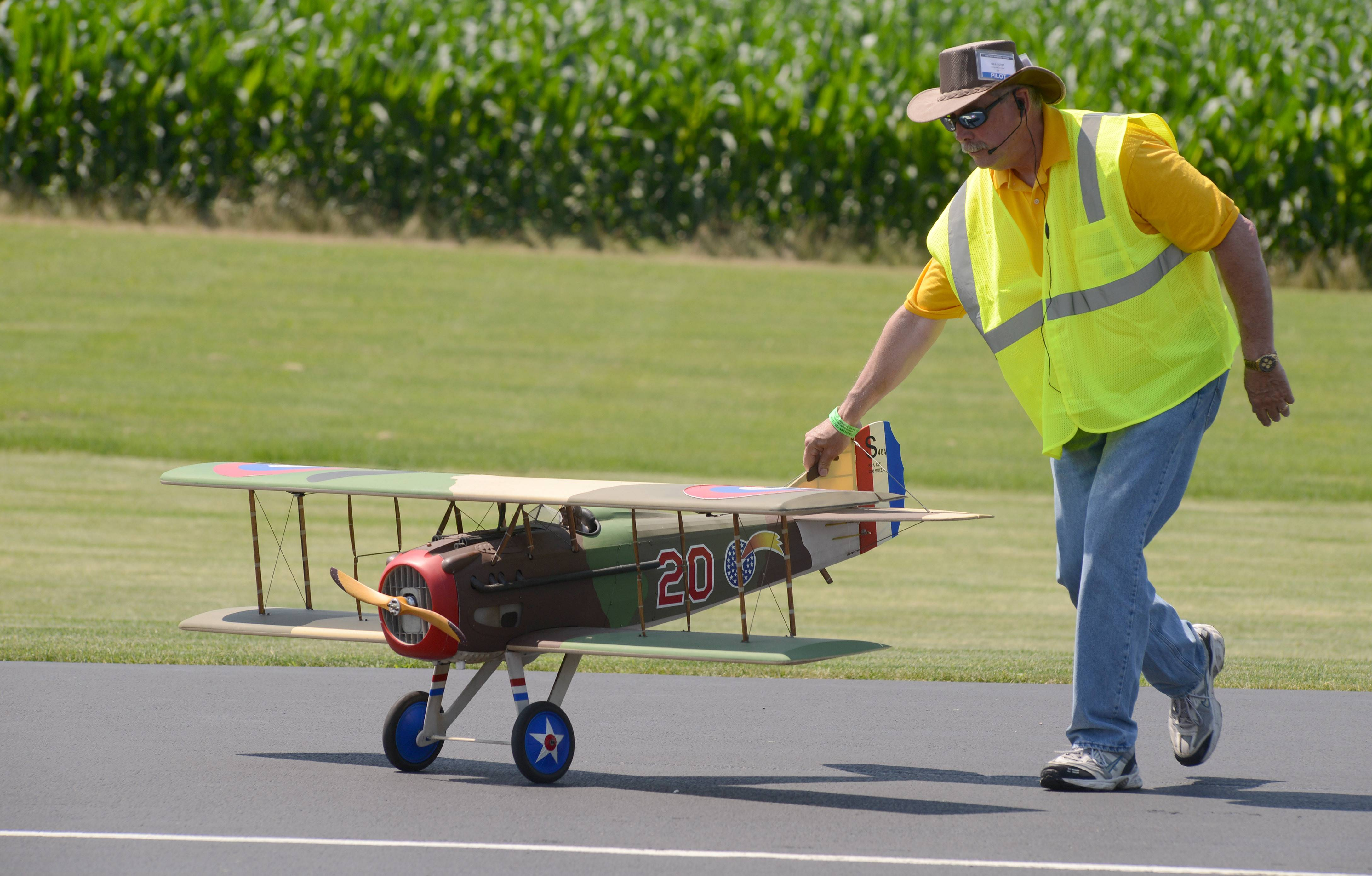 "Bill Suhr of Palatine retrieves a SPAD 13 biplane (World War I era) from the landing strip, serving as ""air boss for retrieval"" at the Fox Valley Aero Club's Windy City Warbird and Classics model airplane show Friday in St. Charles. Suhr, a member of the club for the past three years, has been flying model planes since 1975. The plane is owned by Chad Asmus of Menomonie, Wisconsin, who has flown with the club several times."