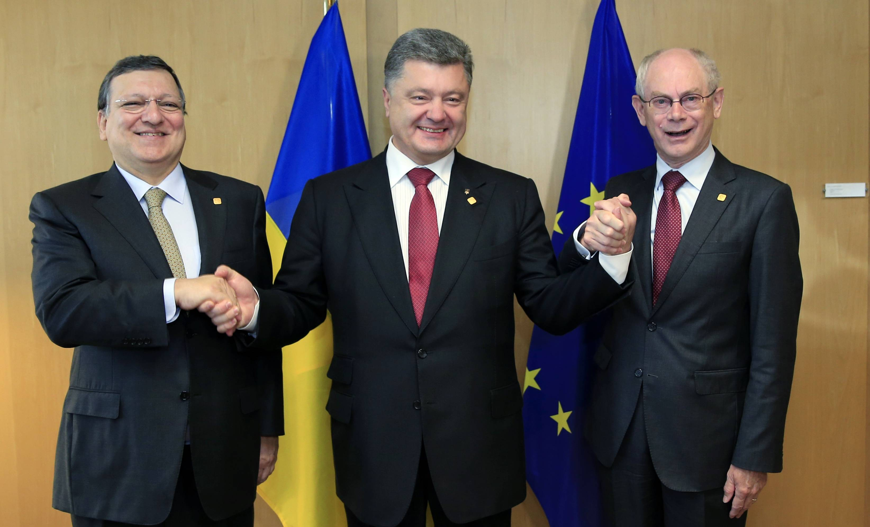 "Ukraine's President Petro Poroshenko, center, poses with European Commission President Jose Manuel Barroso, left, and European Council President Herman Van Rompuy during an EU Summit in Brussels on Friday. Ukrainian President Petro Poroshenko has signed up to a trade and economic pact with the European Union, saying it may be the ""most important day"" for his country since it became independent from the Soviet Union."