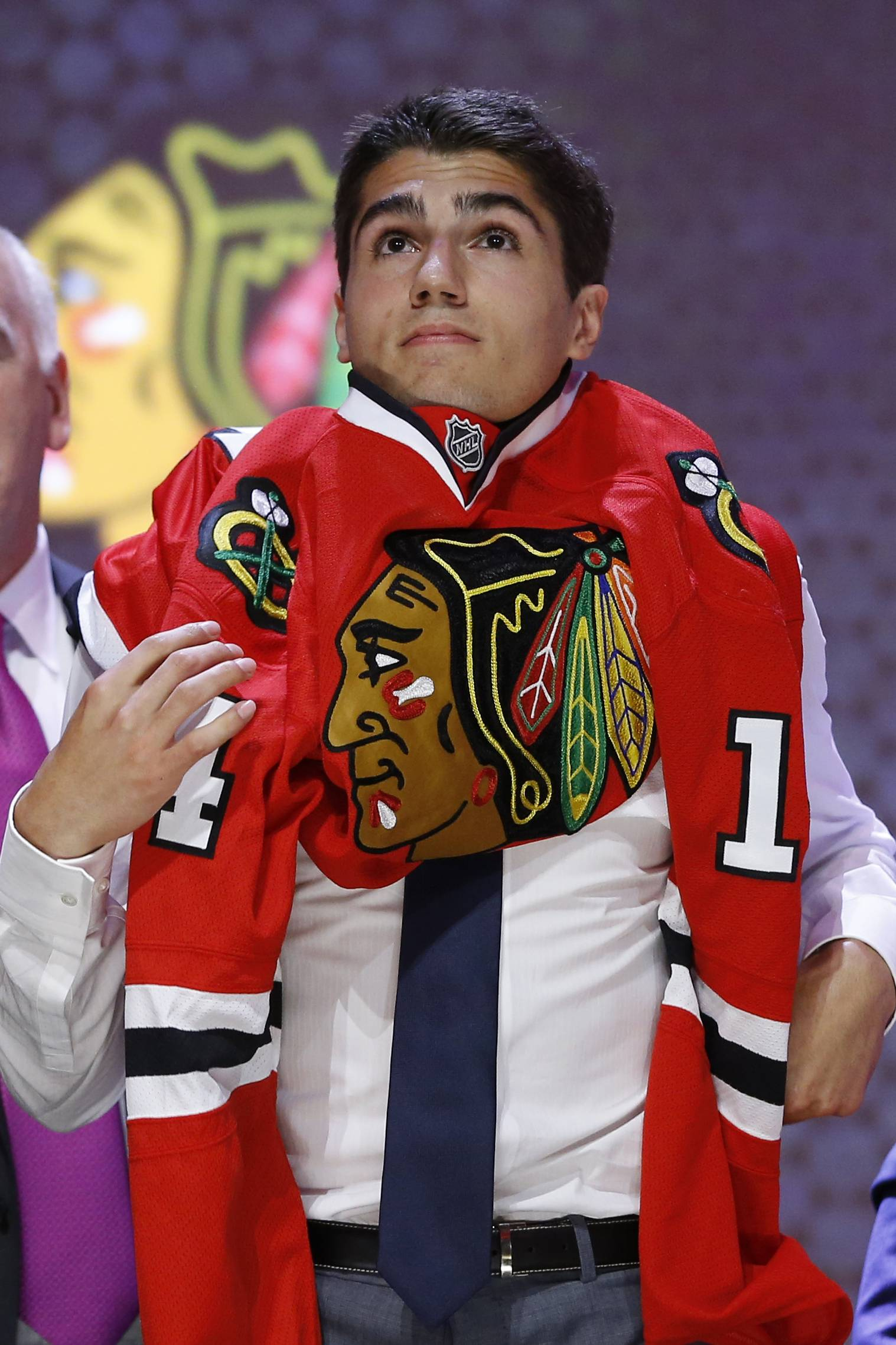 Nick Schmaltz pulls on a Chicago Blackhawks sweater after being chosen 20th overall during the first round of the NHL hockey draft, Friday, June 27, 2014, in Philadelphia. (AP Photo/Matt Slocum)