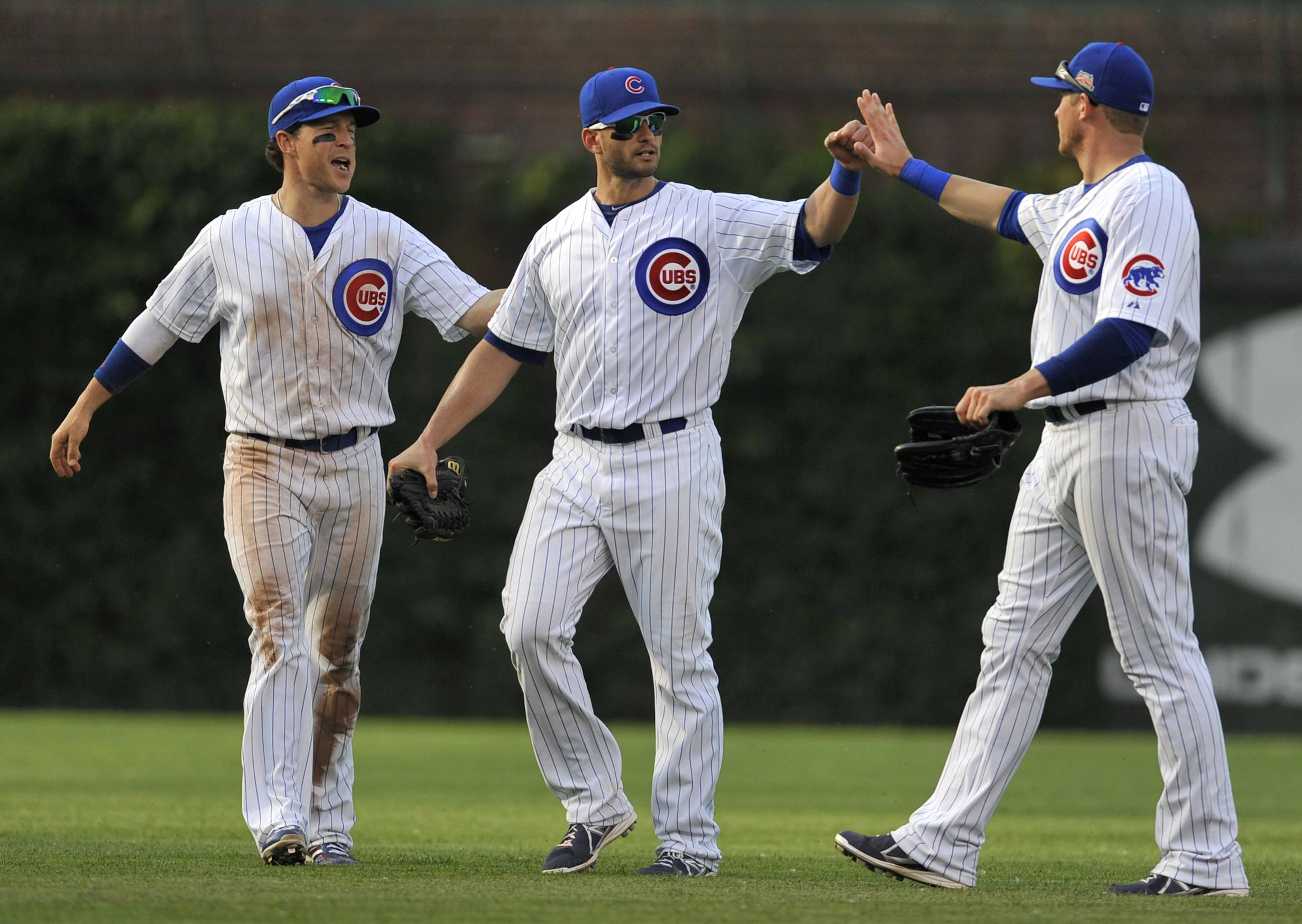 Cubs outfielders Justin Ruggiano, left, Chris Coghlan, center, and Ryan Sweeney right, celebrate after the Cubs defeated the Washington Nationals 7-2 on Friday. The Cubs are 21-17 since May 17, but playing above .500 baseball will be difficult if — as expected — the team makes a flurry of trades before July 31.