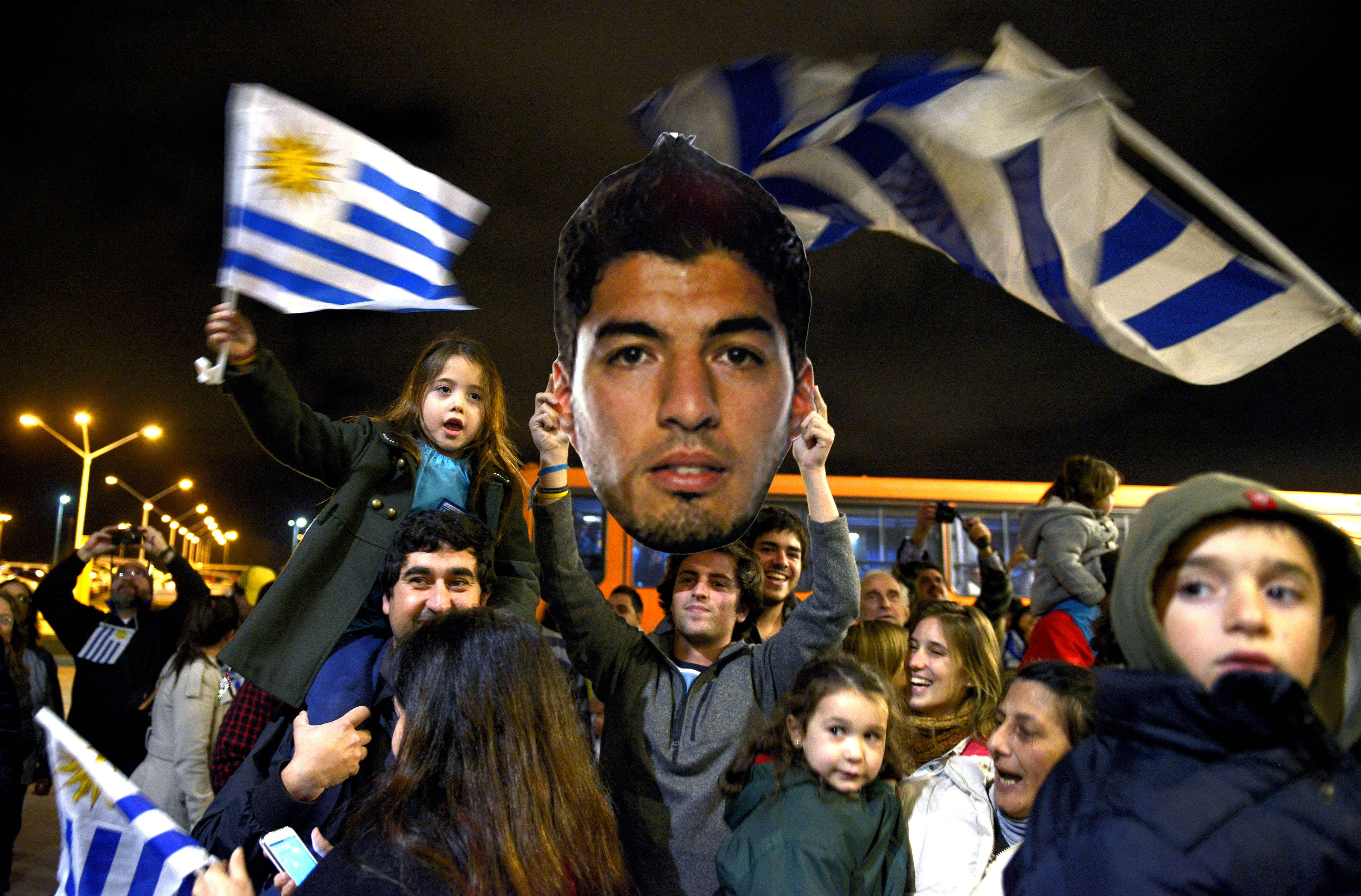 Fans of Uruguay's national soccer team await the arrival of Uruguay player Luis Suarez at Carrasco International Airport in the outskirts of Montevideo, Uruguay, Thursday, June 26, 2014. The Uruguay forward was banned by FIFA from all football for four months on Thursday for biting an Italian opponent.