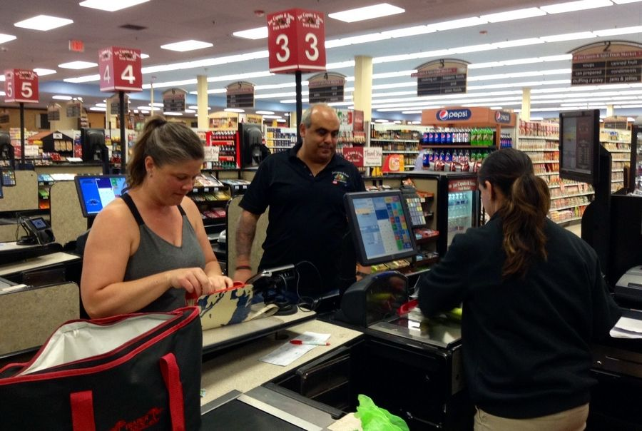 Owner Nat Caputo looks on as the first customer, Regina Fortman, checks out at the new Arlington Heights market.