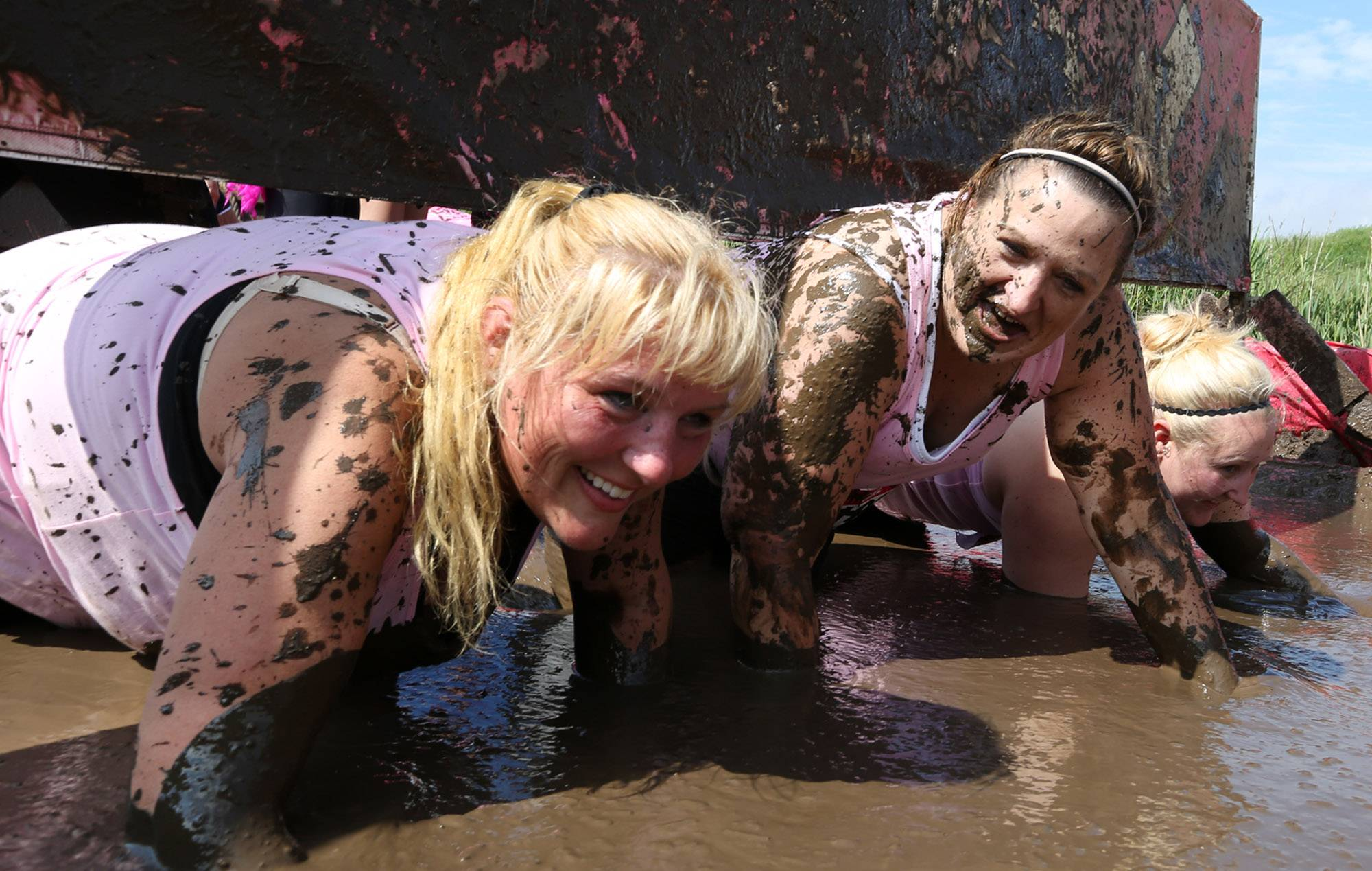 Jennifer Elkins of Ingleside, with Fight Dirty for Donna K, left, crawls under an obstacle and through muddy water with team members during the Dirty Girl Mud Run Saturday at the Lake County Fairgrounds in Grayslake.