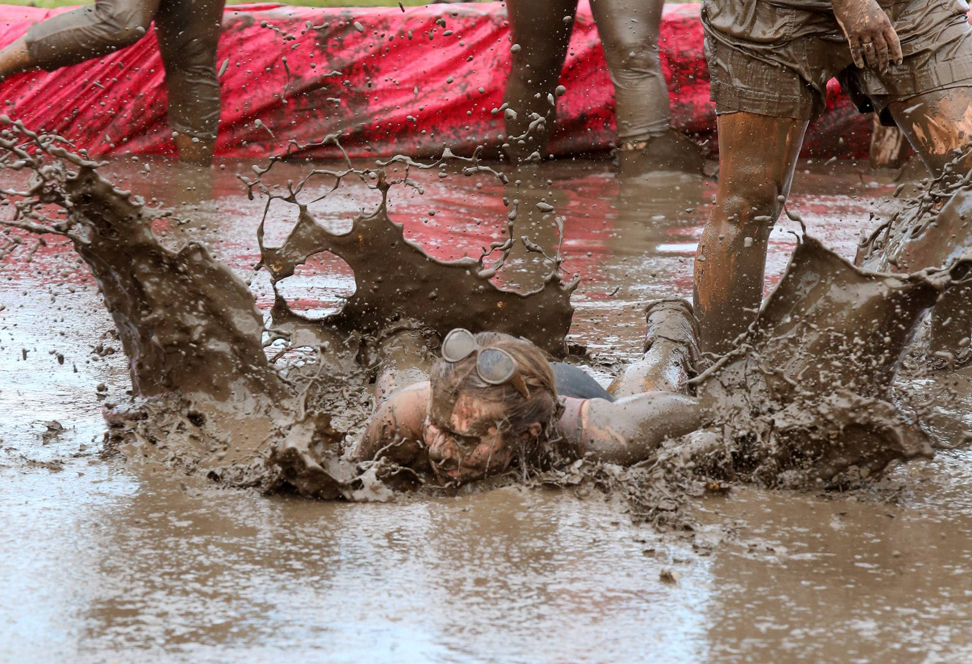 Nicole Moss of Kenosha, Wis., falls in muddy water near the finish of the Dirty Girl Mud Run Saturday at the Lake County Fairgrounds in Grayslake.
