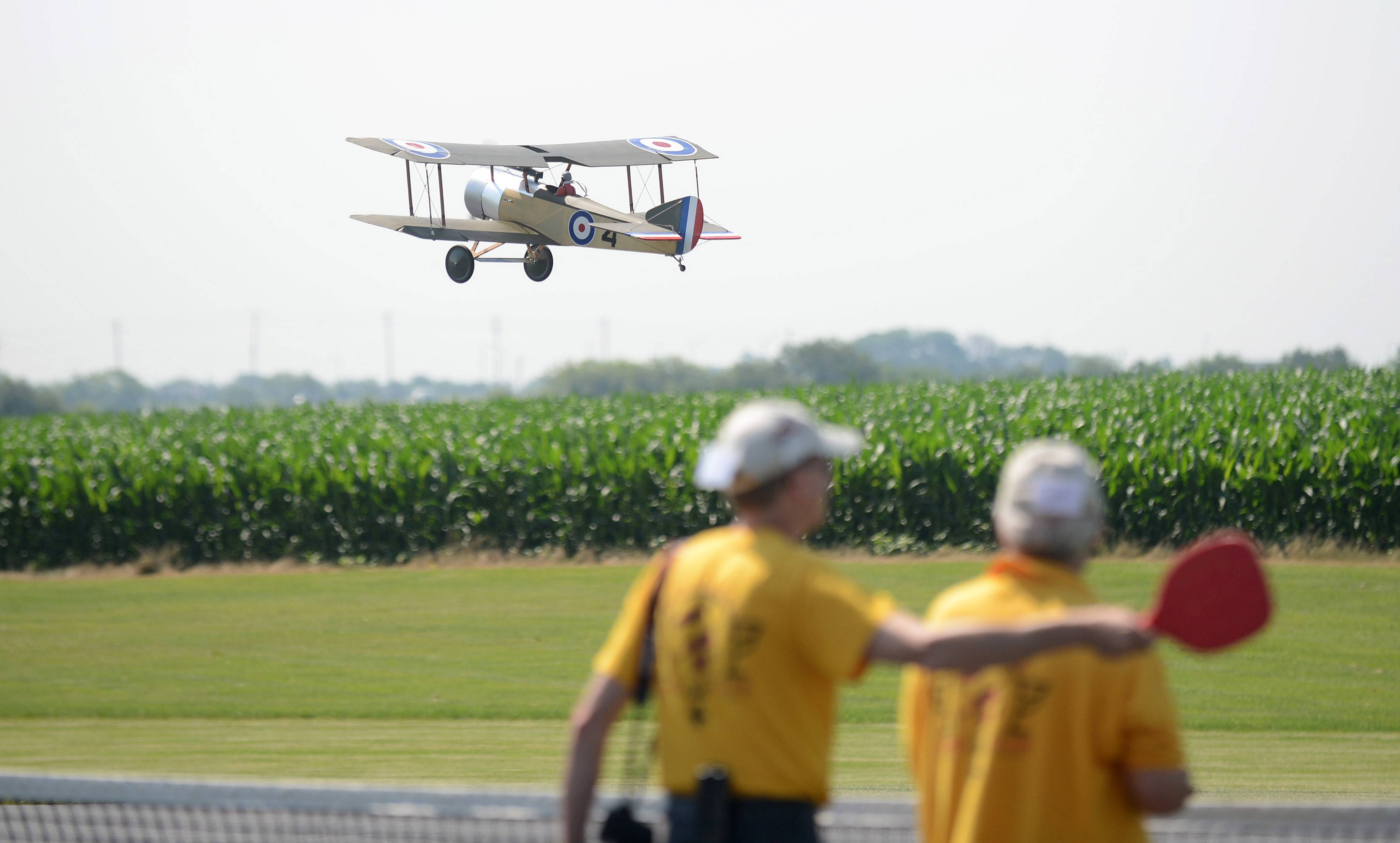 A biplane makes a showing pass near the runway as another pilot and spotter signal a request to land during the Fox Valley Aero Club's Windy City Warbird and Classics model airplane show.