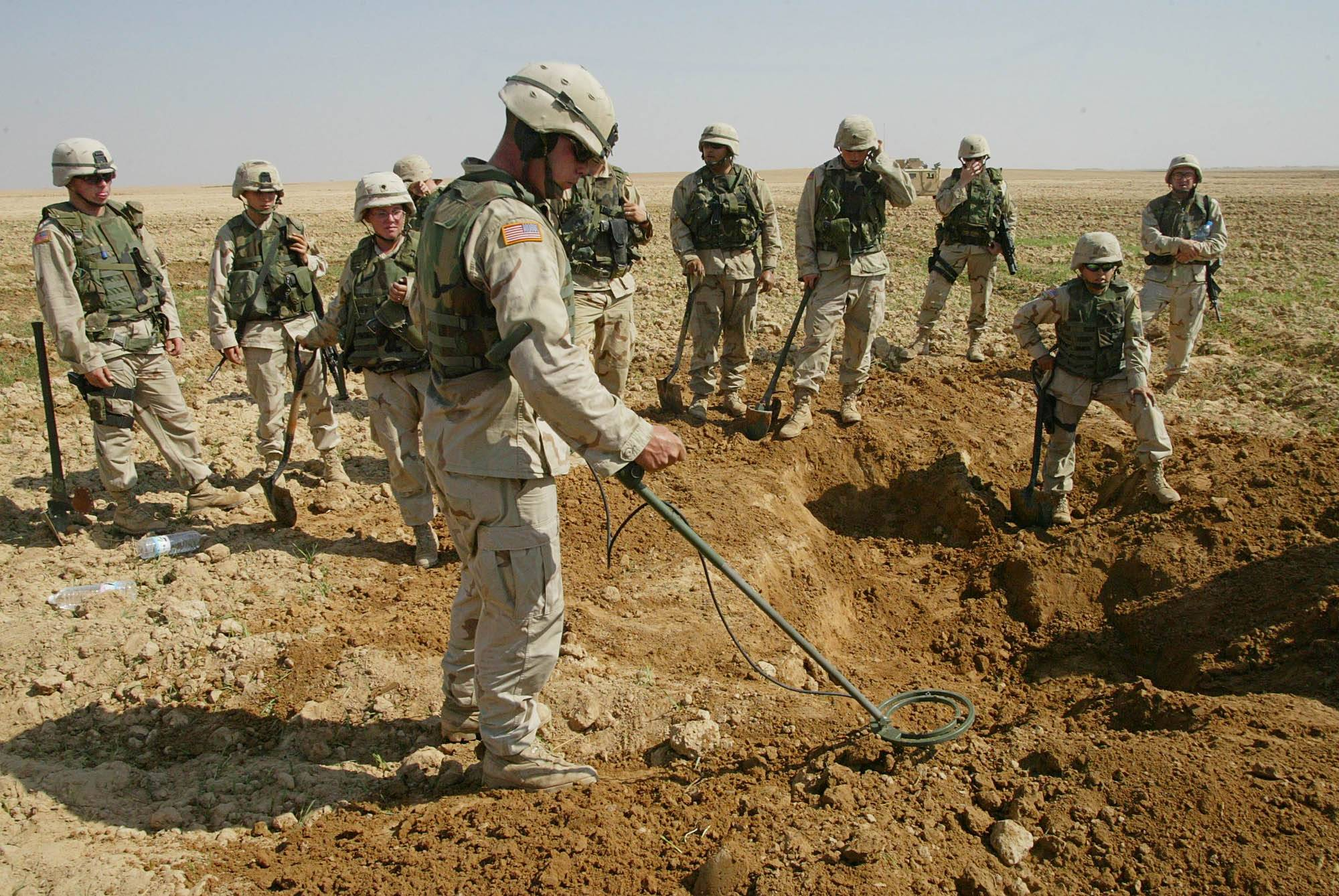Soldiers from the U.S. Army's 720th Military Police Battalion watch as a mine sweeper look for weapons in a hole they dug during a raid on a farmland just outside Tikrit, Iraq.