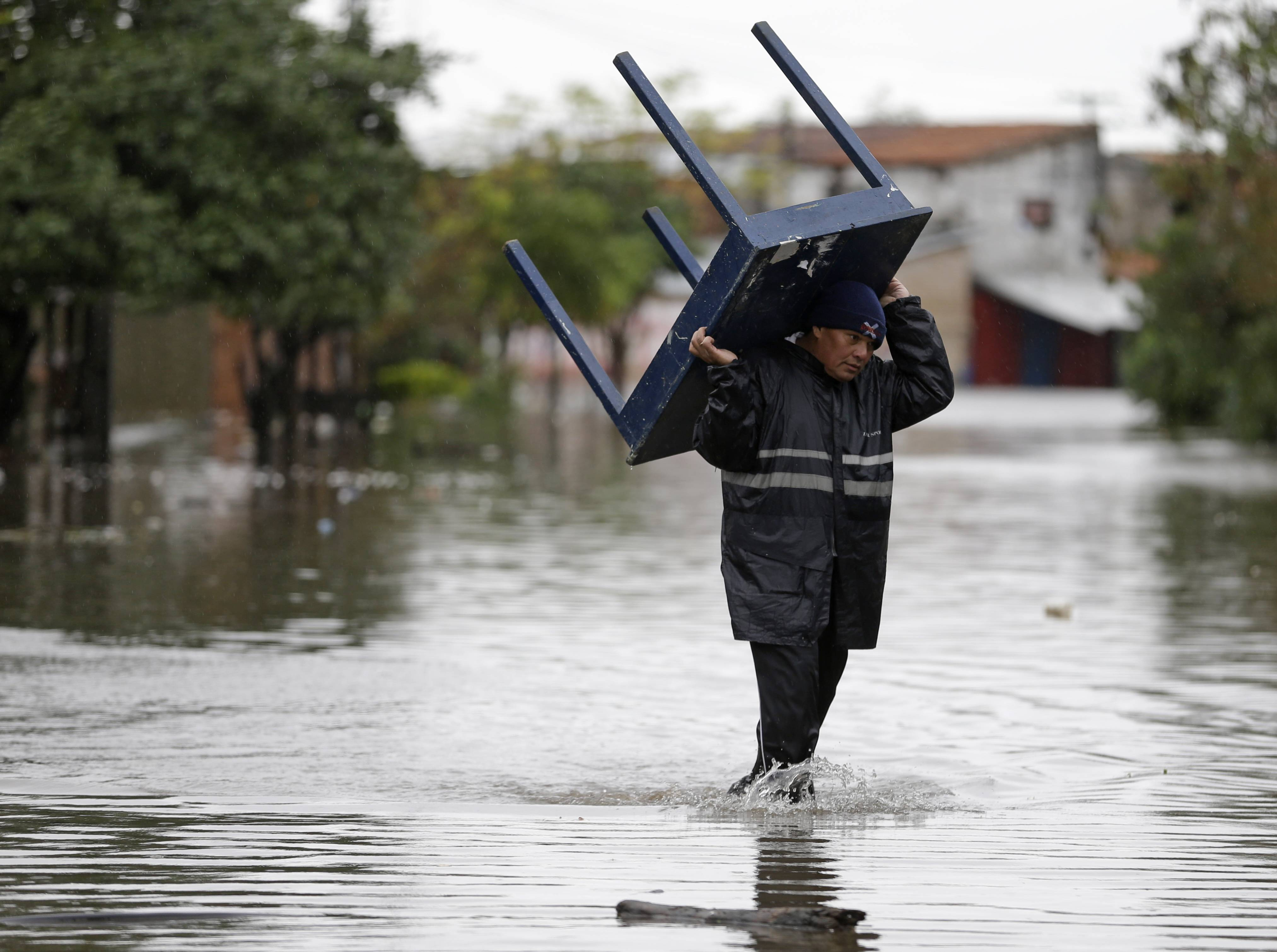 A man carries a table through a flooded street Friday in the Tacumbu neighborhood of Asuncion, Paraguay.