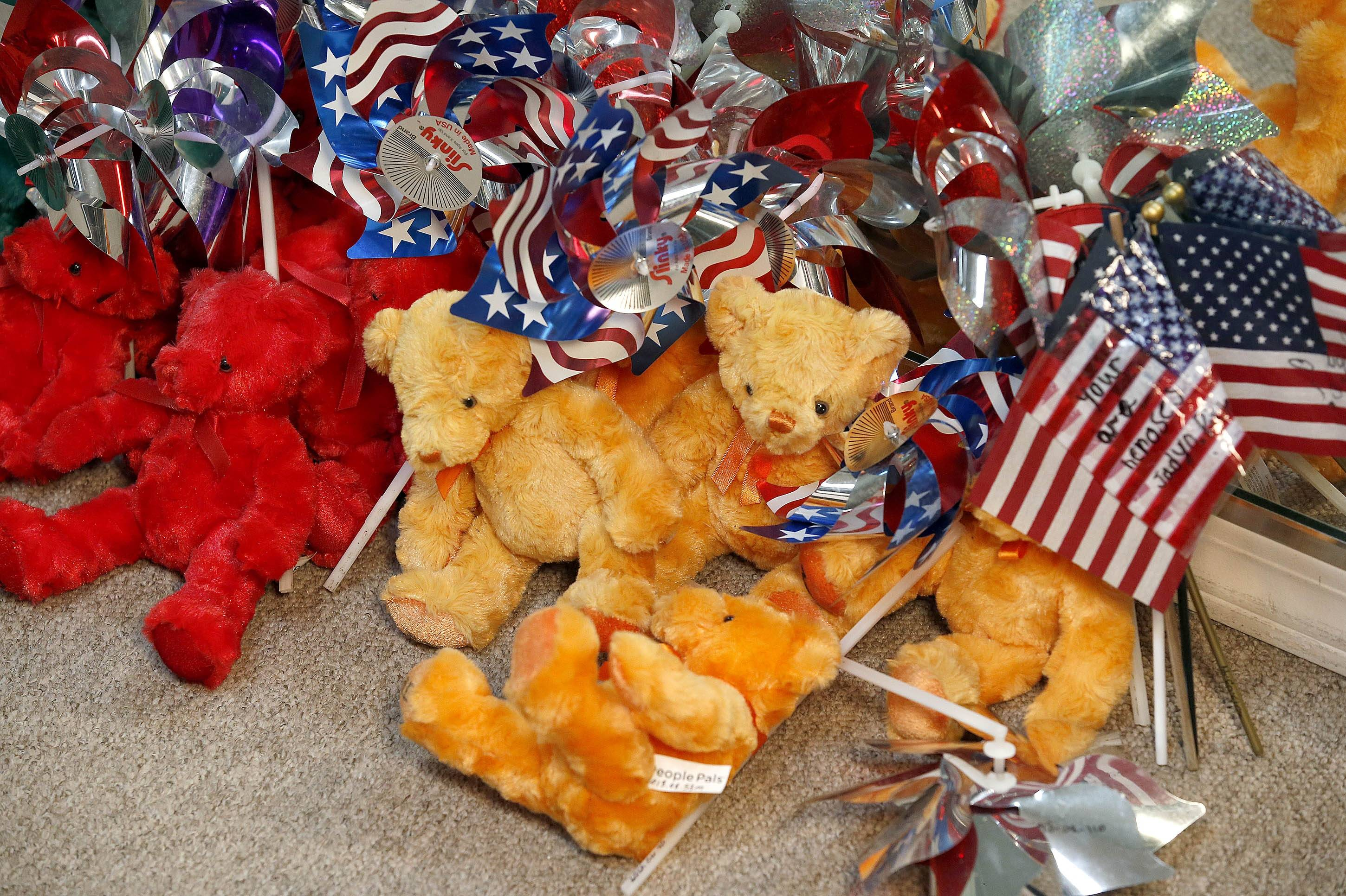 Just some of the dozens of teddy bears saved for the Tribute Fence Preservation Project honoring the 19 Granite Mountain Hotshots who were killed nearly a year ago fighting an Arizona wildfire on Tuesday, June 24, 2014, in Prescott, Ariz.