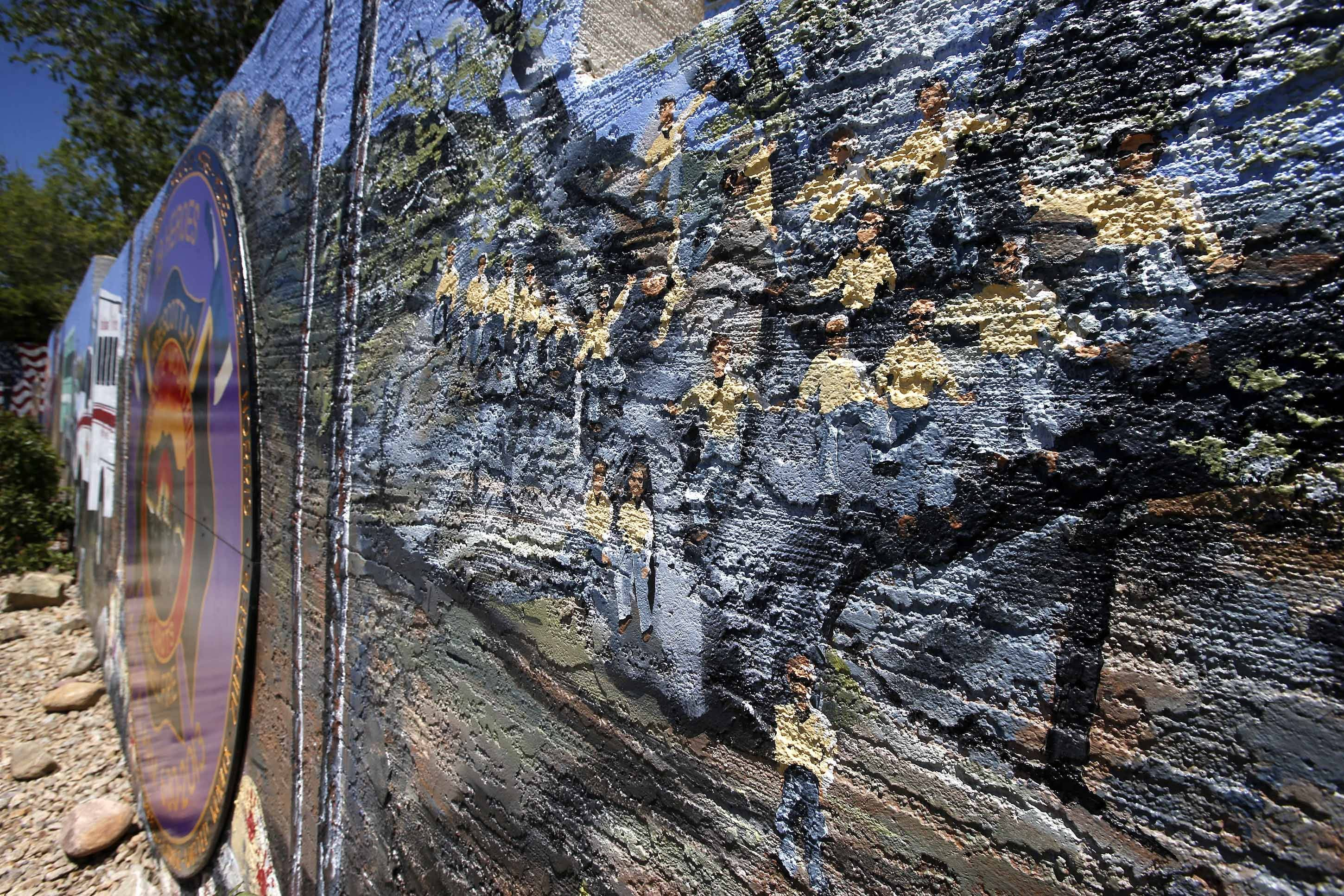 A painted mural by Juliana Hutchins covers a retaining wall memorial honoring the 19 Granite Mountain Hotshots who died nearly a year ago fighting an Arizona wildfire on Tuesday, June 24, 2014, in Prescott, Ariz. The mural also honors other first responders.
