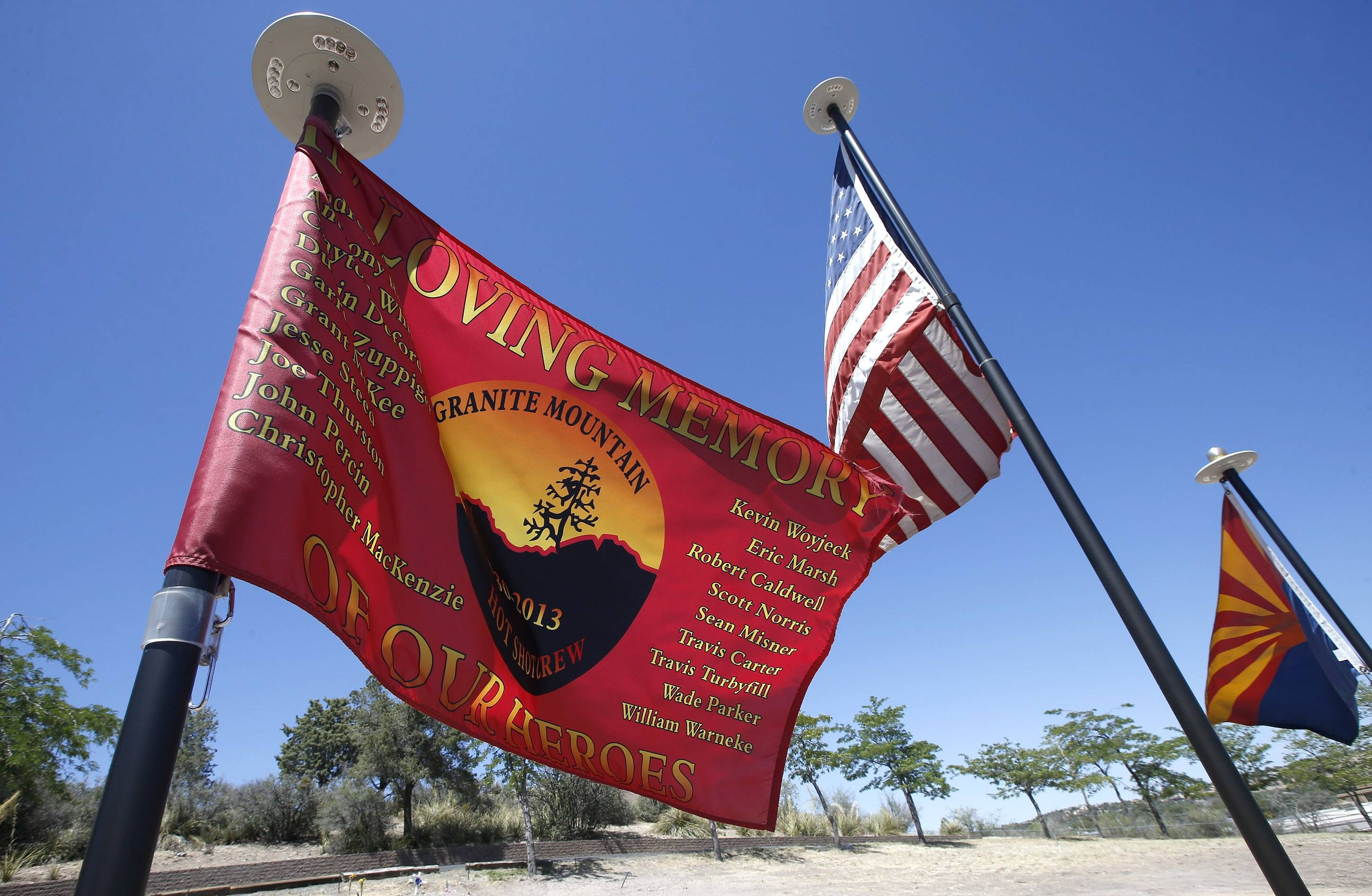 Flags fly at a memorial gravesite at Pioneer Cemetery where the 19 Granite Mountain Hotshots are honored nearly a year after all were killed fighting a wildfire on Tuesday, June 24, 2014, in Prescott, Ariz.
