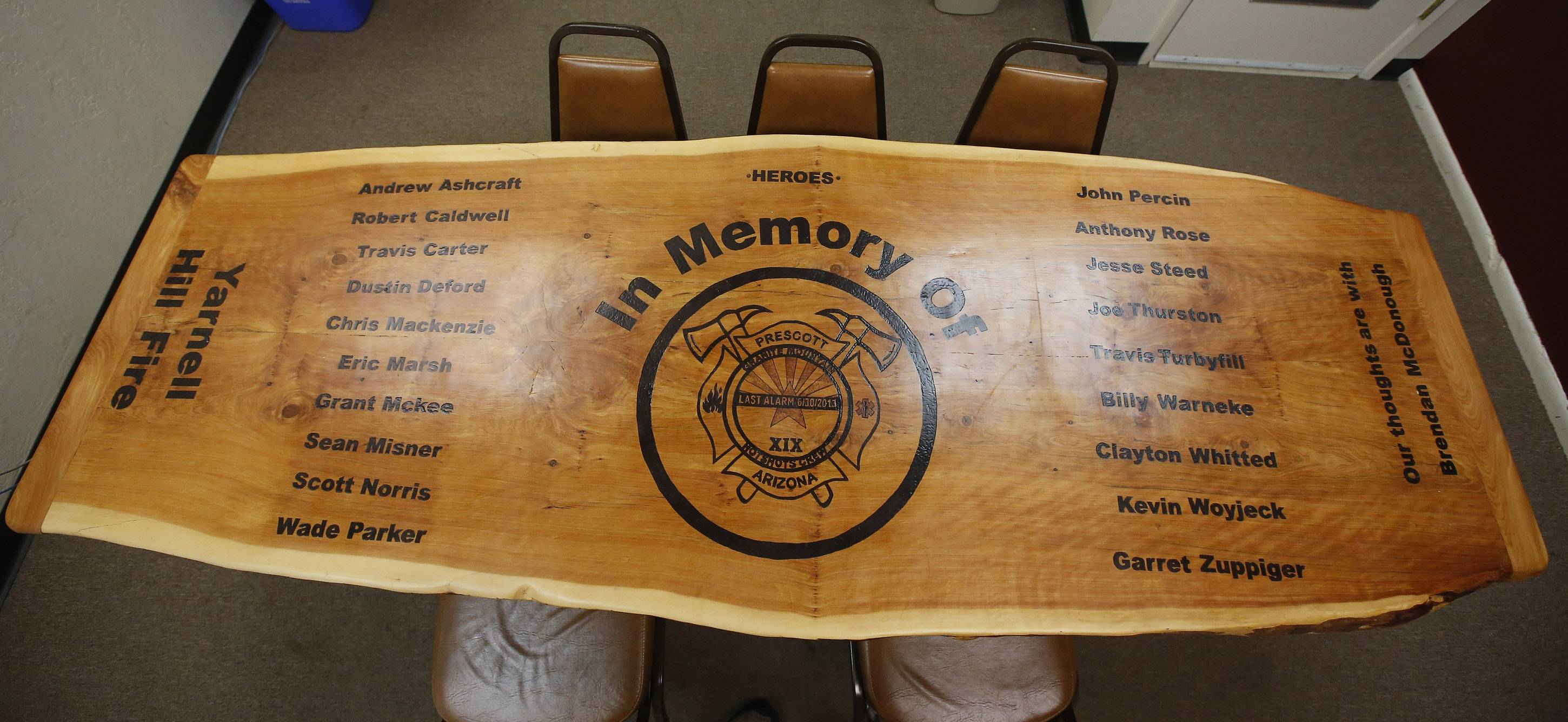 Inside the Granite Mountain Hotshots firehouse there are several memorial reminders of the 19 hotshot crew members killed fighting a wildfire nearly a year ago, this one a handmade wooden table, on Tuesday, June 24, 2014, in Prescott, Ariz.