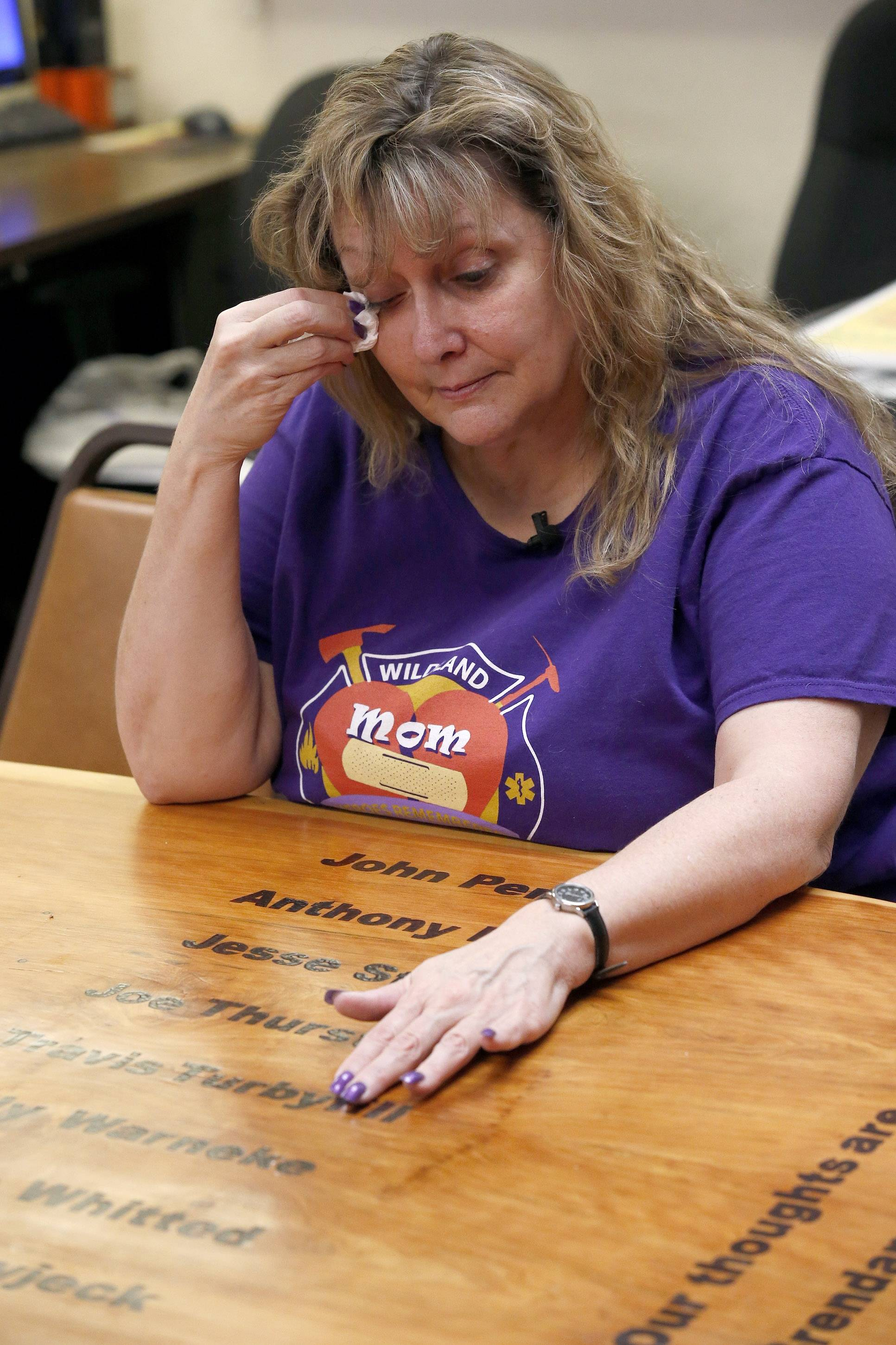 In her first visit back to the firehouse since her son's death, Colleen Turbyfill, Travis Turbyfill's mother, is overcome with emotions as she rubs her fingers over her son's name on an inscribed wooden table, as she recalls memories of her and her son, who was killed along with 18 other hotshots during a wildfire nearly a year ago, on Tuesday, June 24, 2014, in Prescott, Ariz.