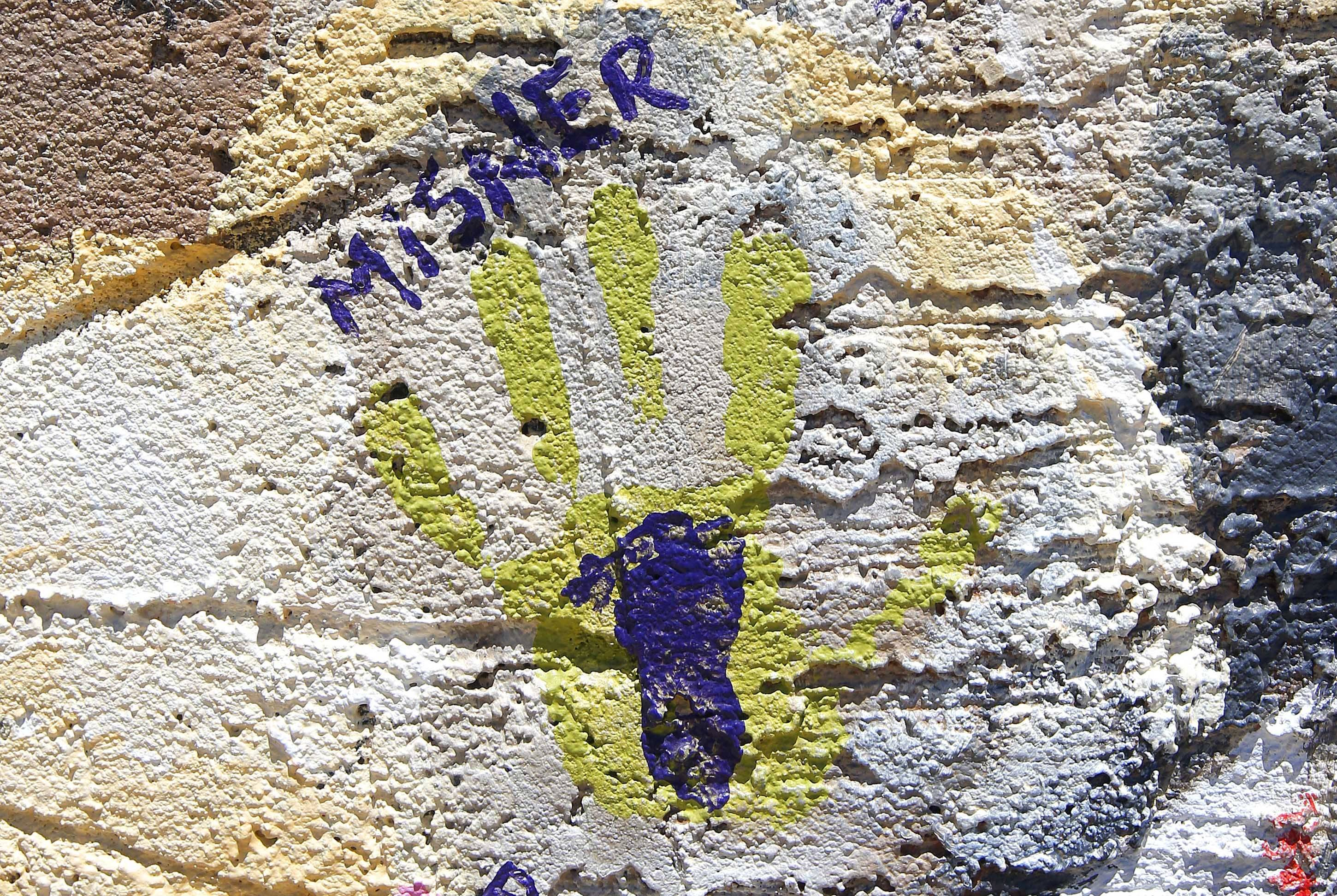 The handprint of Amanda Misner, wife of Sean Misner who perished as one of the 19 Granite Mountain Hotshots fighting an Arizona wildfire, dwarfs the footprint of the son he never knew, as the paint imprints are part of a memorial mural near the Pioneer Cemetery honoring all the hotshots who died on Tuesday, June 24, 2014, in Prescott, Ariz. Amanda Misner was seven months pregnant with the younger Sean Jaxon Herbert Misner, when her husband was killed.