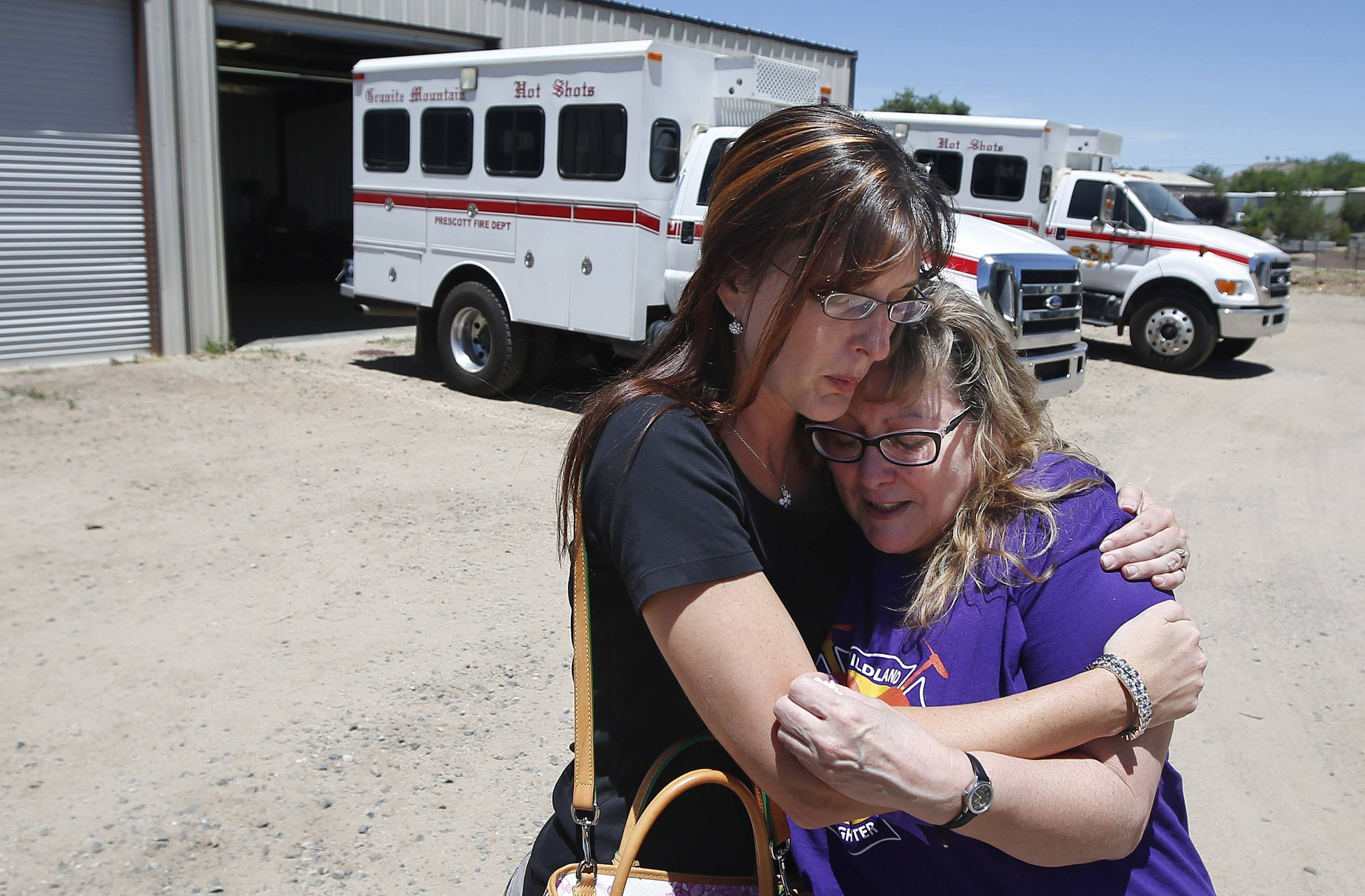 In her first visit to the firehouse in Prescott, Ariz., since her son's death, Colleen Turbyfill, right, Travis Turbyfill's mother, gets a hug from Katie Cornelius, Prescott Fire Department volunteer exhibit curator for the Tribute Fence Preservation Project, after Turbyfill visited the Granite Mountain Hotshots crew vehicle buggy where her son Travis sat before he was killed along with 18 other hotshots in a wildfire almost a year ago.