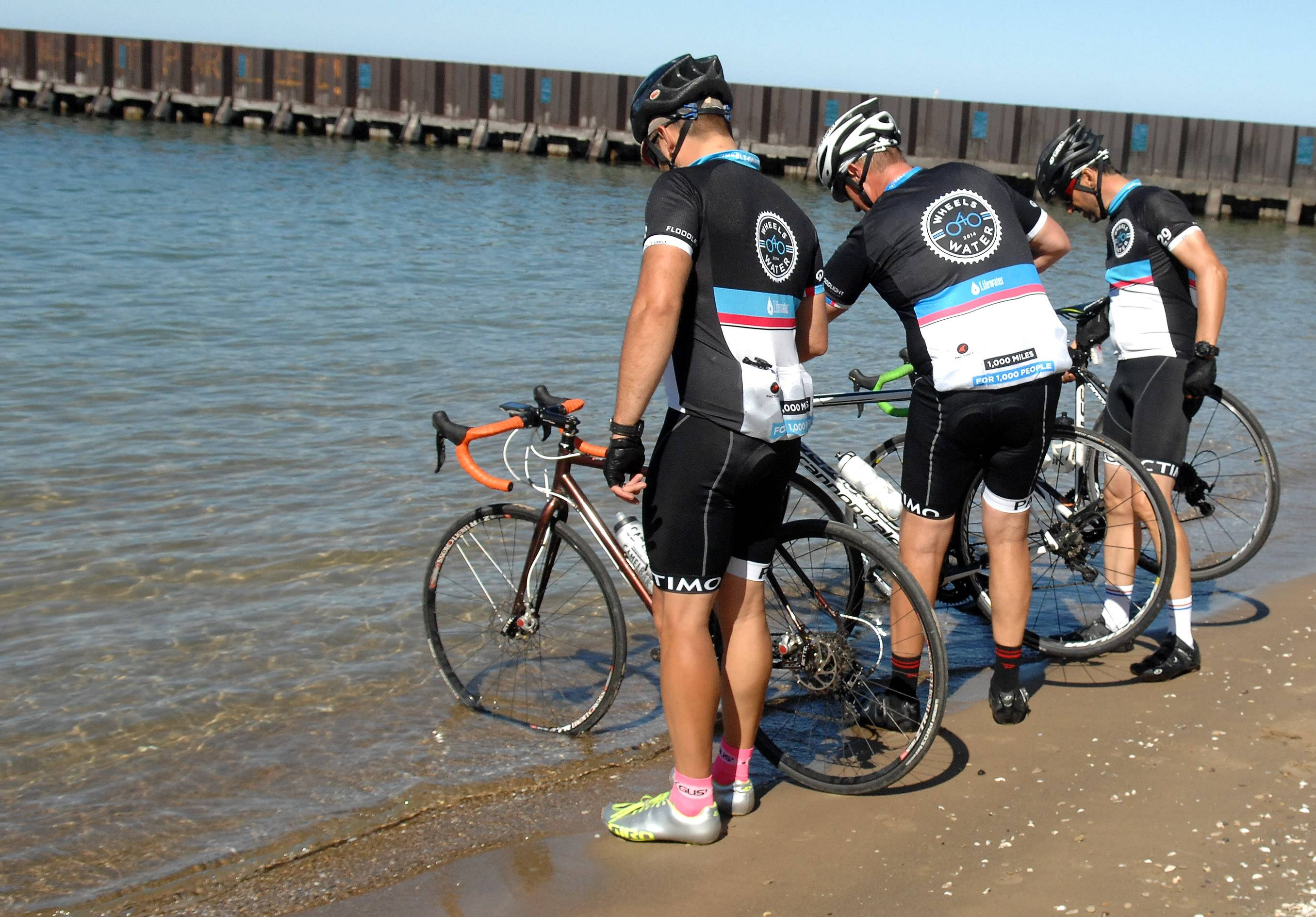 Justin Ahrens, left, Ryan Connary and Brian MacDonald dip their front tires in Lake Michigan as a ceremonial ending to their 1,207-mile ride earlier this month. They started their trip by dipping their rear tires in Boston Harbor 15 days earlier.