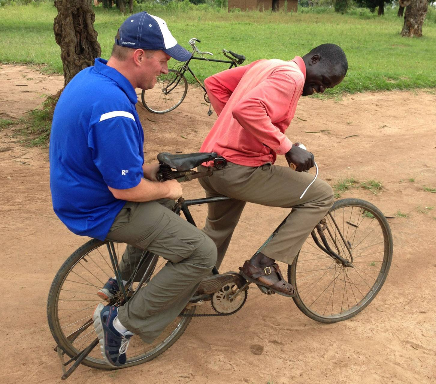 Justin Ahrens of Batavia, left, gets a ride from a local during a trip to Africa.