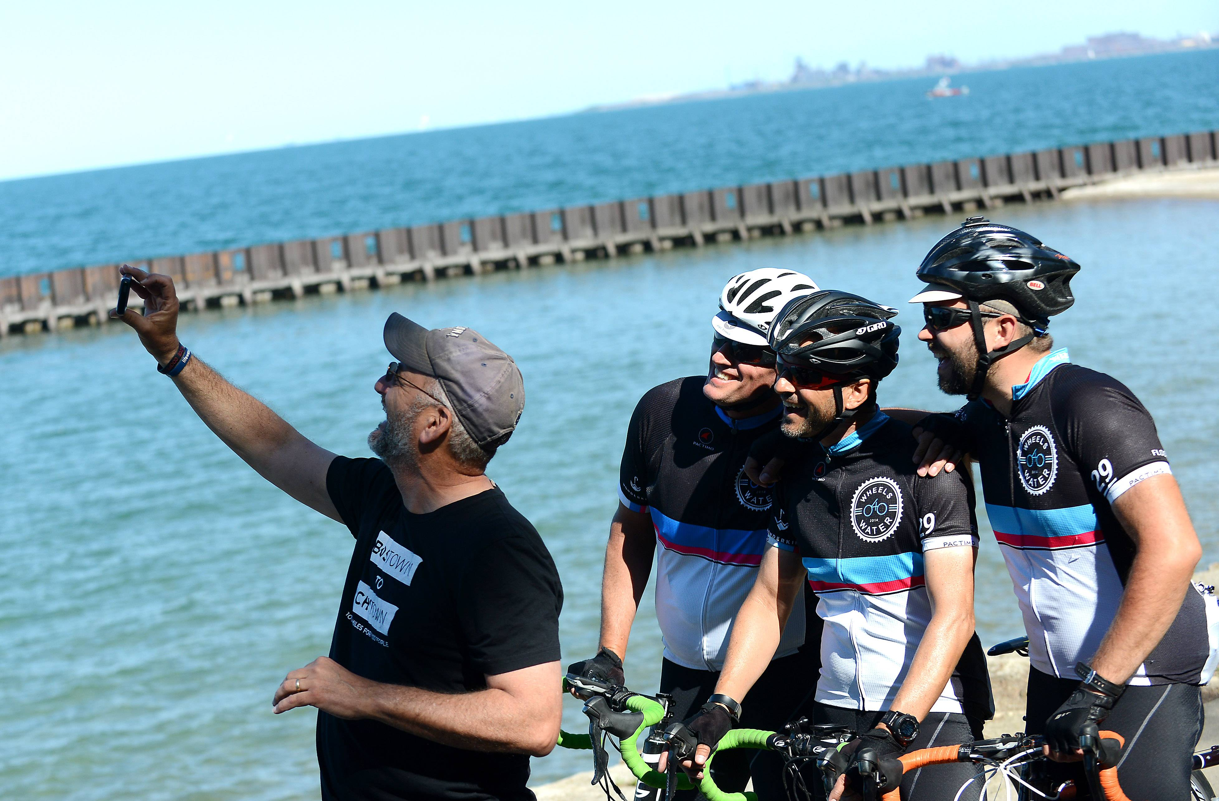 Tony Narducci, who captained the support van for the Wheels4Water ride, takes a selfie with riders Justin Ahrens, left, Brian MacDonald and Ryan Connary.