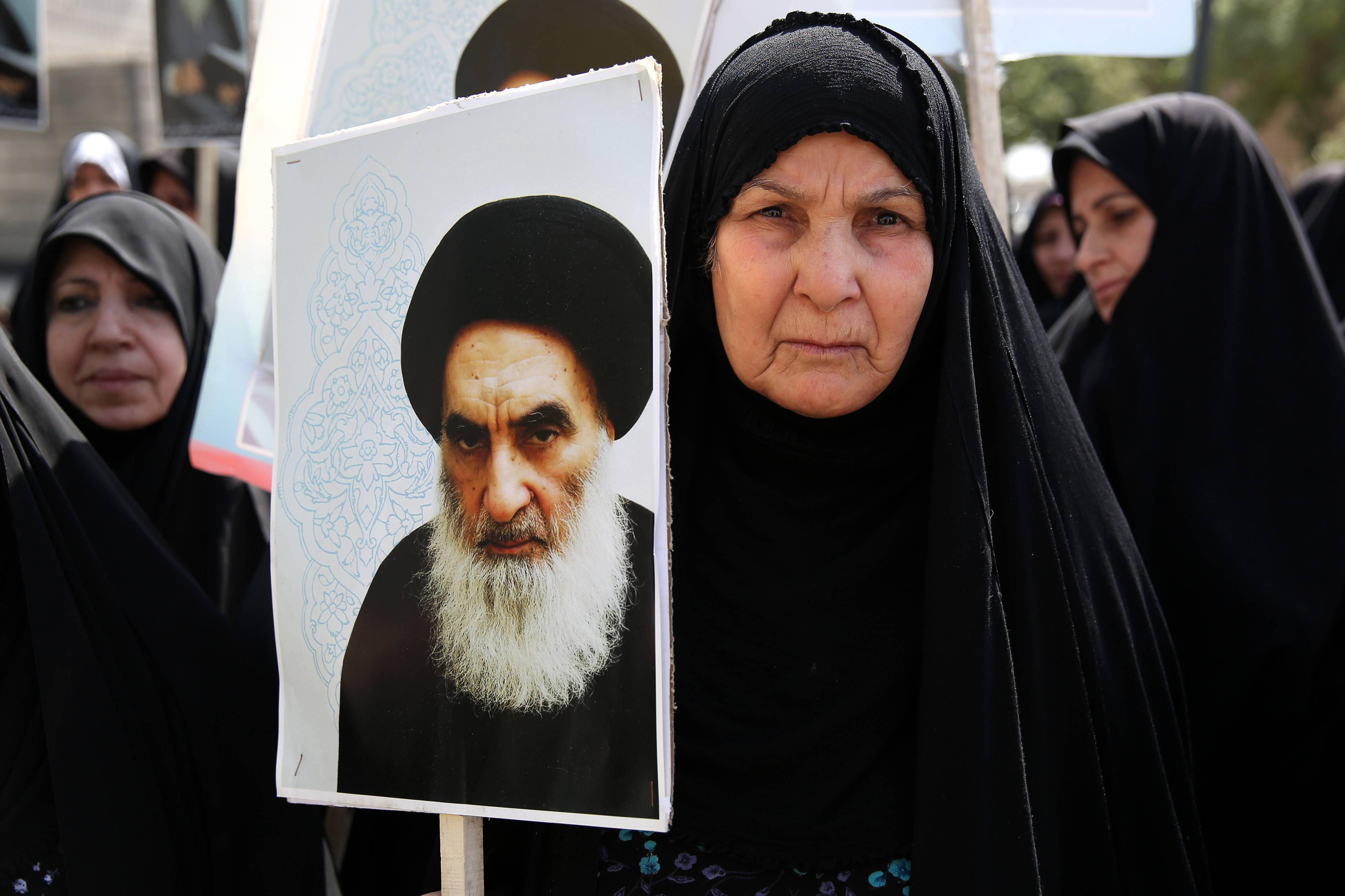 An Iraqi woman living in Iran holds a poster of the Grand Ayatollah Ali al-Sistani, Iraq's top Shiite cleric, in a demonstration against Sunni militants of the al-Qaida-inspired Islamic State of Iraq and the Levant, or ISIL, and to support Ayatollah al-Sistani, in Tehran, Iran. Prominent Shiite leaders pushed Thursday for the removal of Iraqi Prime Minister Nouri al-Maliki as parliament prepared to start work next week on putting together a new government, under intense U.S. pressure to rapidly form a united front against an unrelenting Sunni insurgent onslaught.