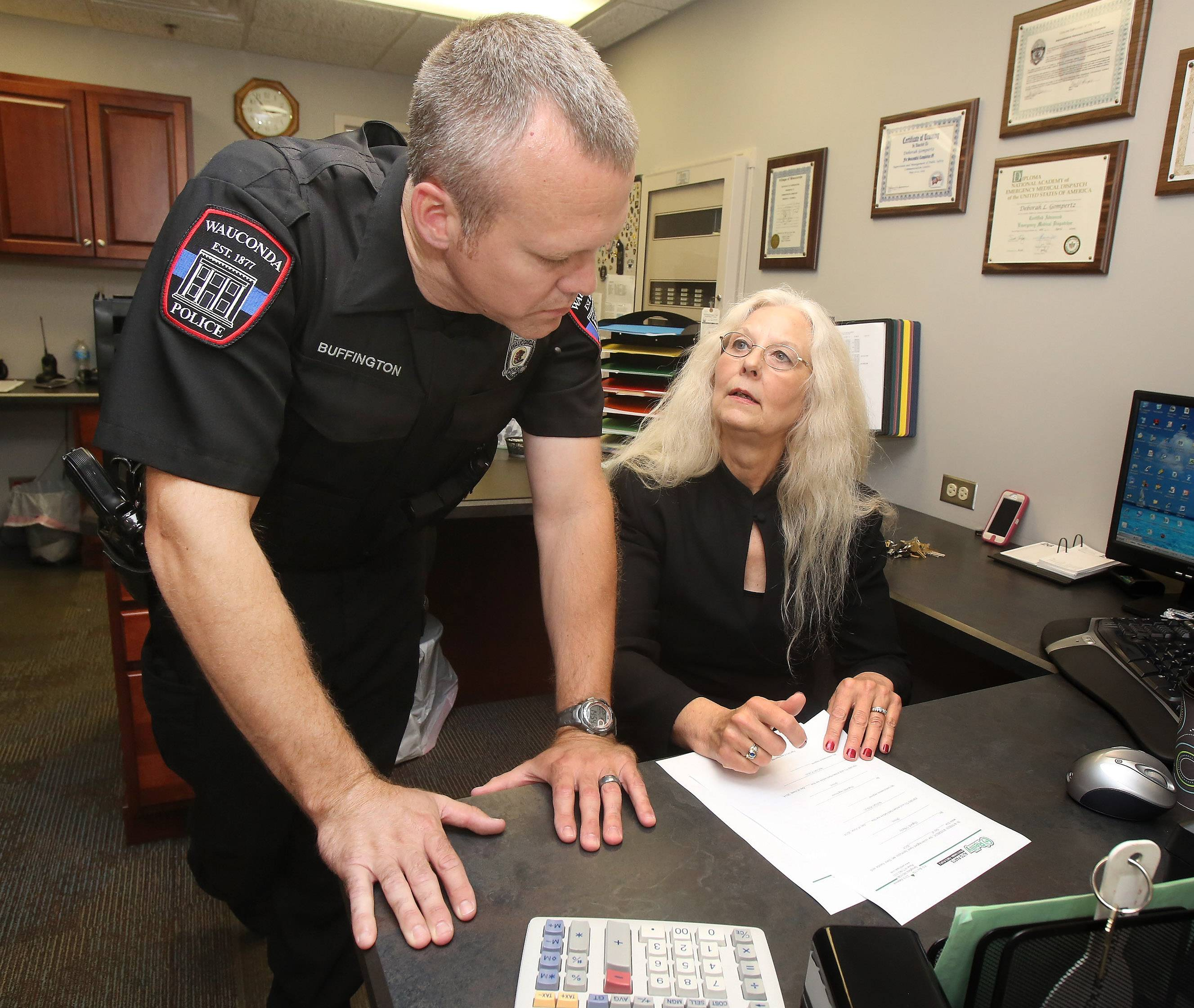 Wauconda Police Department Executive Assistant Deborah Gompertz talks with police officer Justin Buffington. Gompertz is celebrating 40 years with the department where she started as a dispatcher in June 1974.