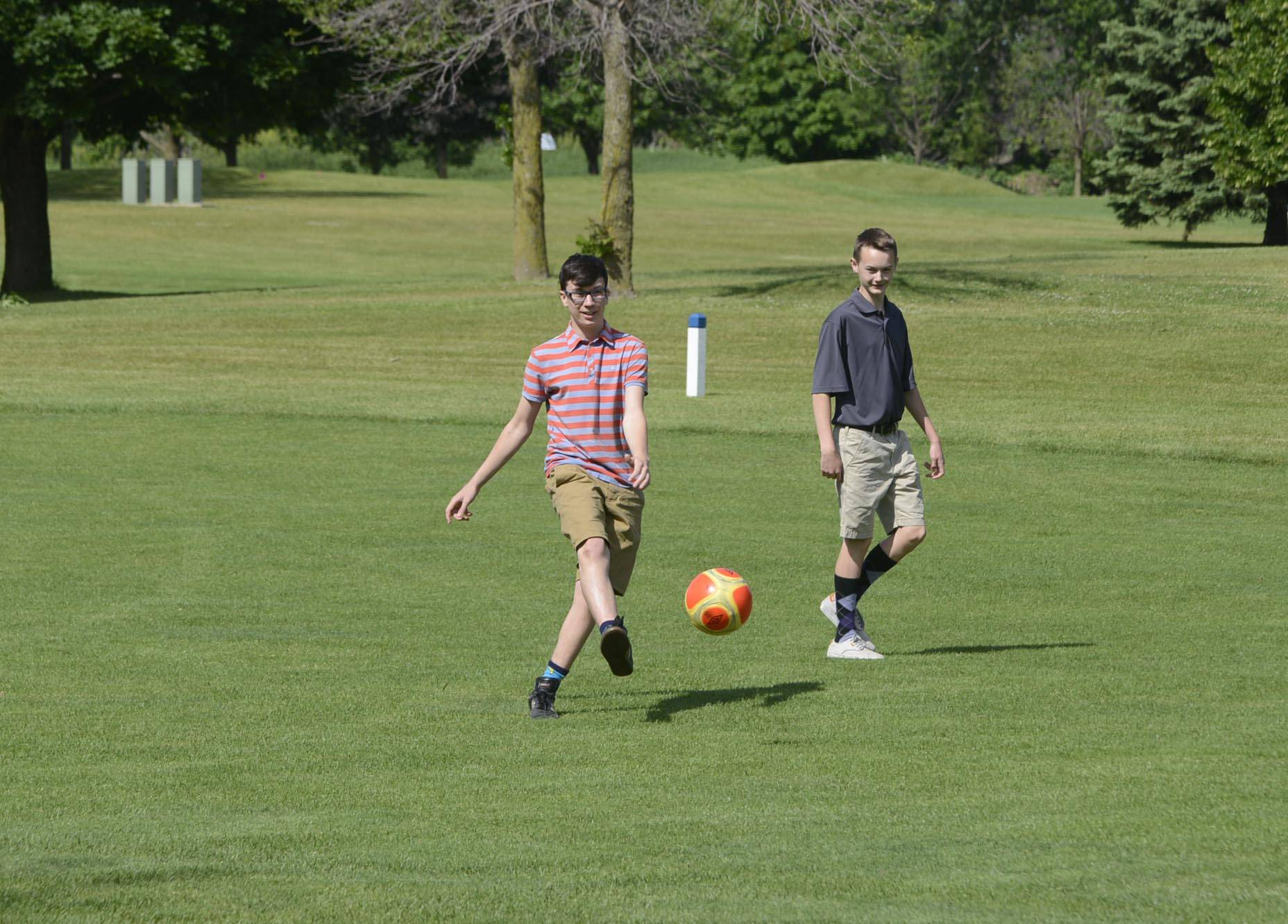 "Alex Lenski kicks from the fairway as he plays FootGolf with friend Garrett Otto, both 16 of Geneva, at Bonnie Dundee Golf Club in Carpentersville. ""It's a great combination of two great sports,"" said Lenski."