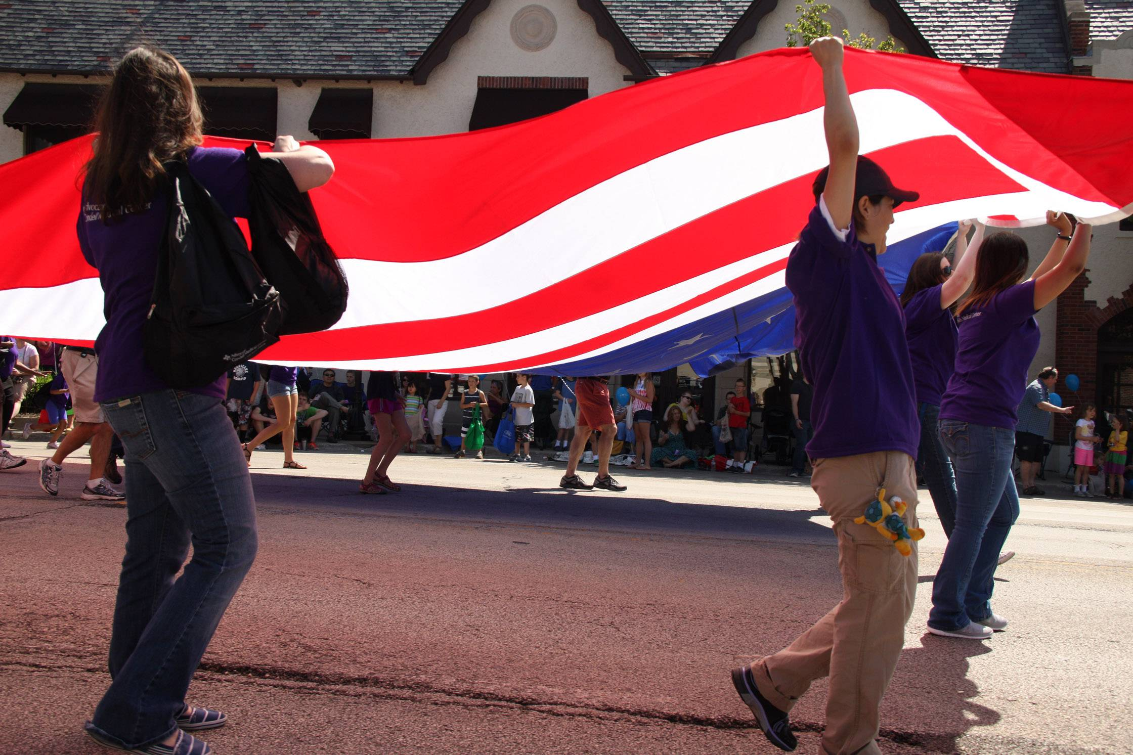 The sunlight brightens an enormous flag as it is carried down the street during the Libertyville Days Parade.