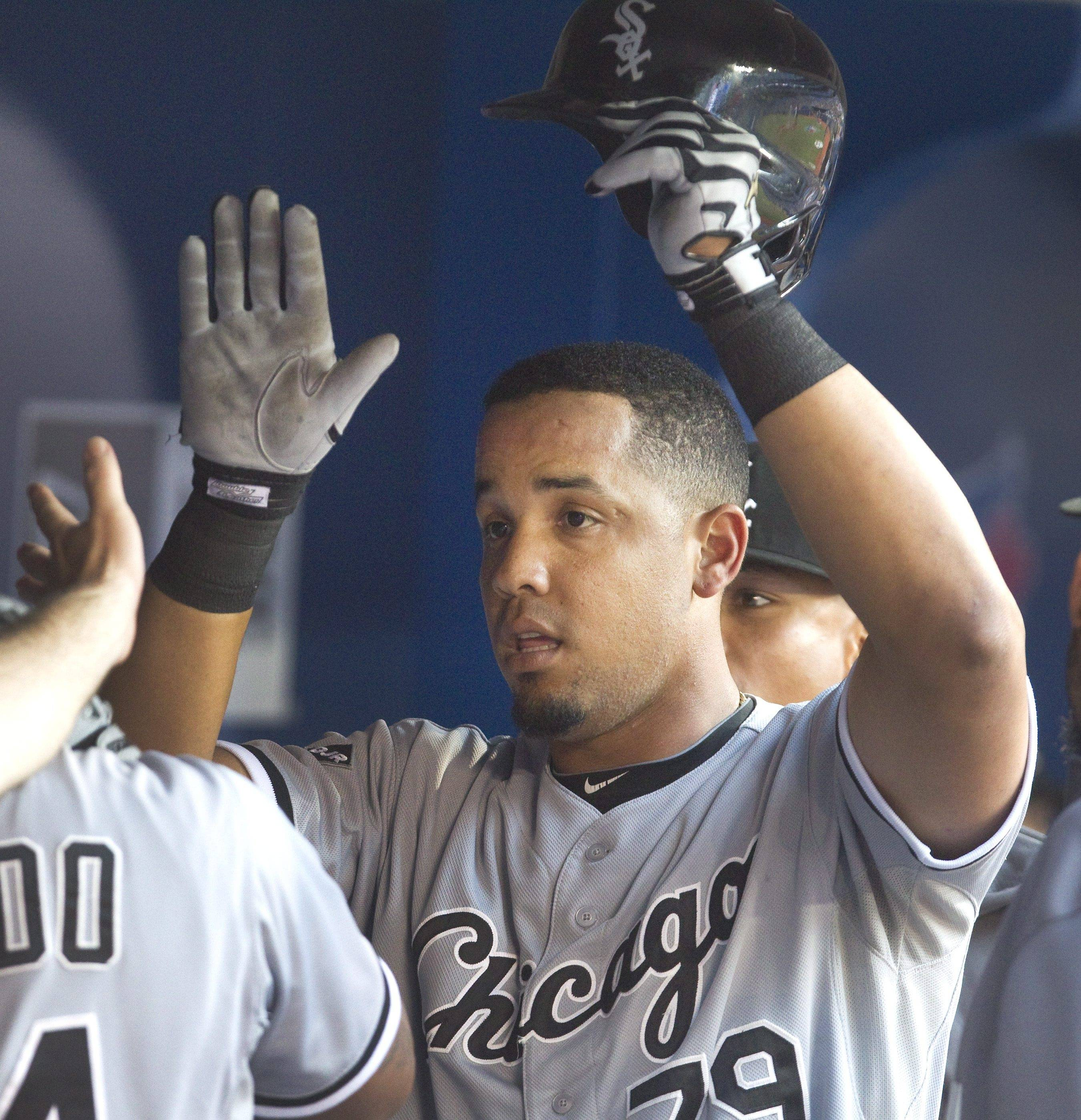Chicago White Sox's Jose Abreu is congratulated in the dugout after he hit a solo home run off Toronto Blue Jays starting pitcher R.A. Dickey during the fifth inning of a baseball game in Toronto on Friday, June 27, 2014.