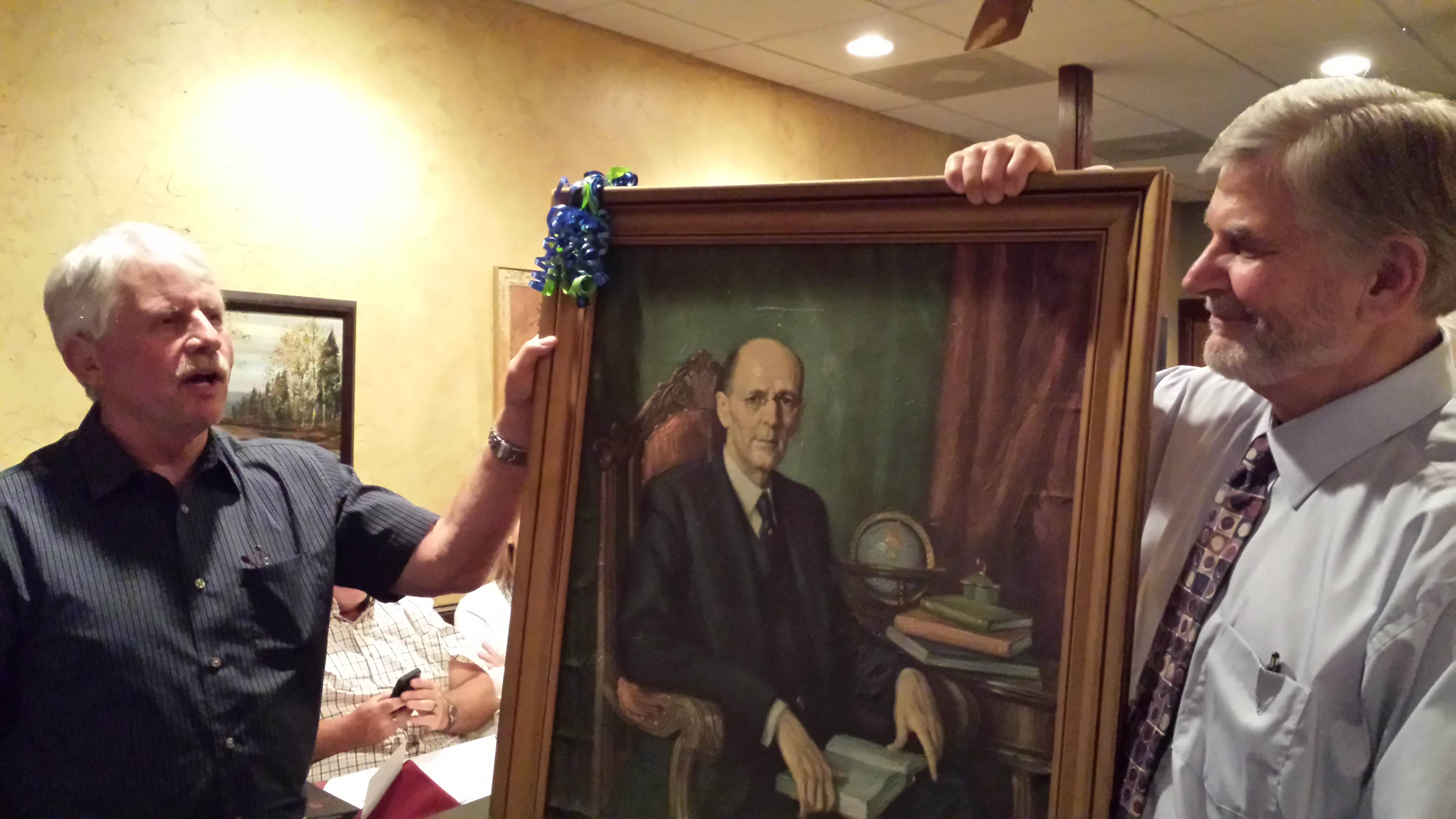Jim Menzer, left, outgoing president of the Rotary Club of Antioch, presents a portrait of Paul Harris, the Chicago attorney who founded Rotary International in 1905, to new president Bob Deiss.