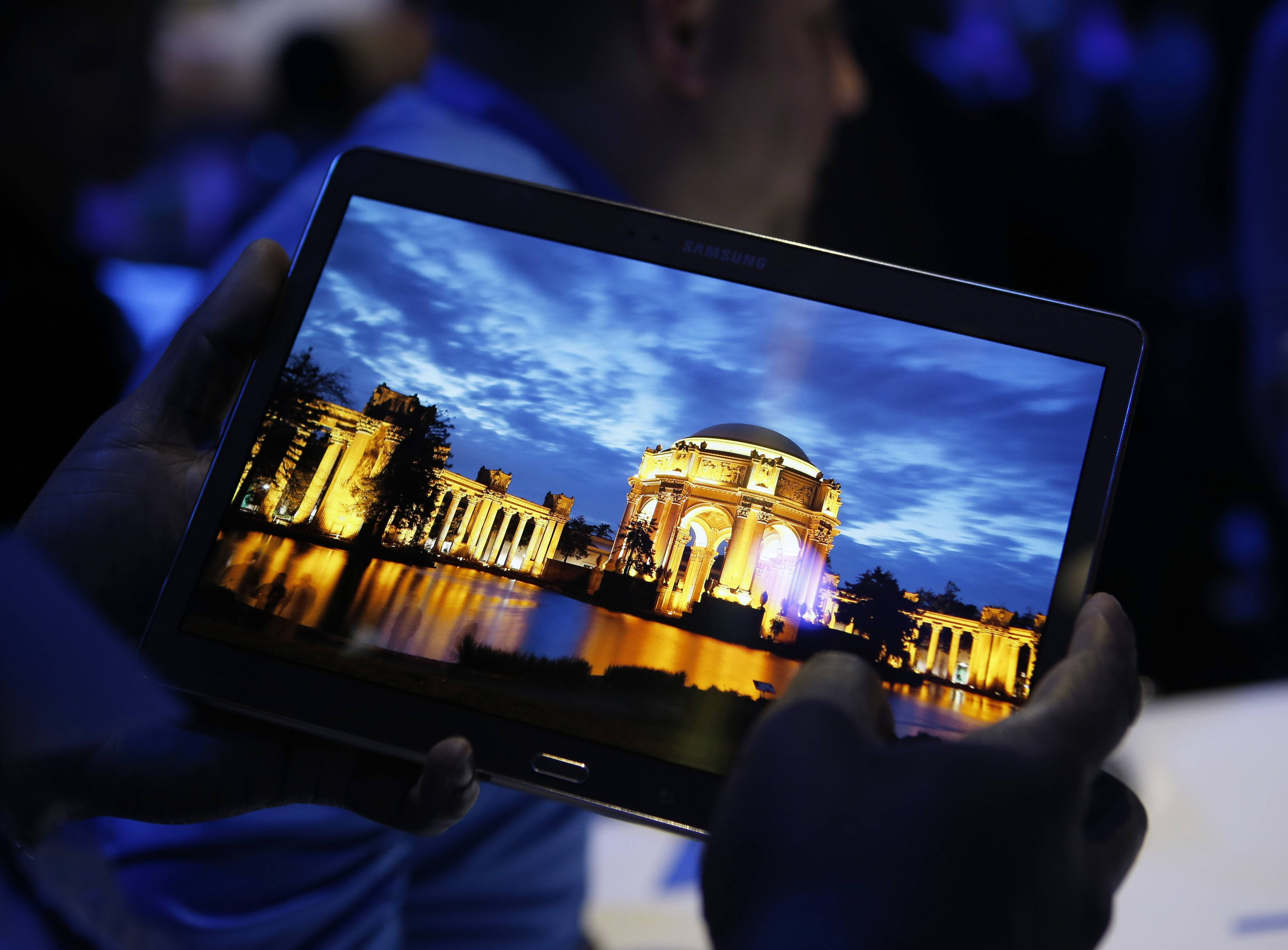 In this Thursday, June 12, 2014, file photo, a member of the media tries out a new Samsung Galaxy Tab S after the tablet's debut at a news conference in New York. The new display technology in Samsung's Galaxy Tab S tablet brings colors to life and reduces the device's bulk.