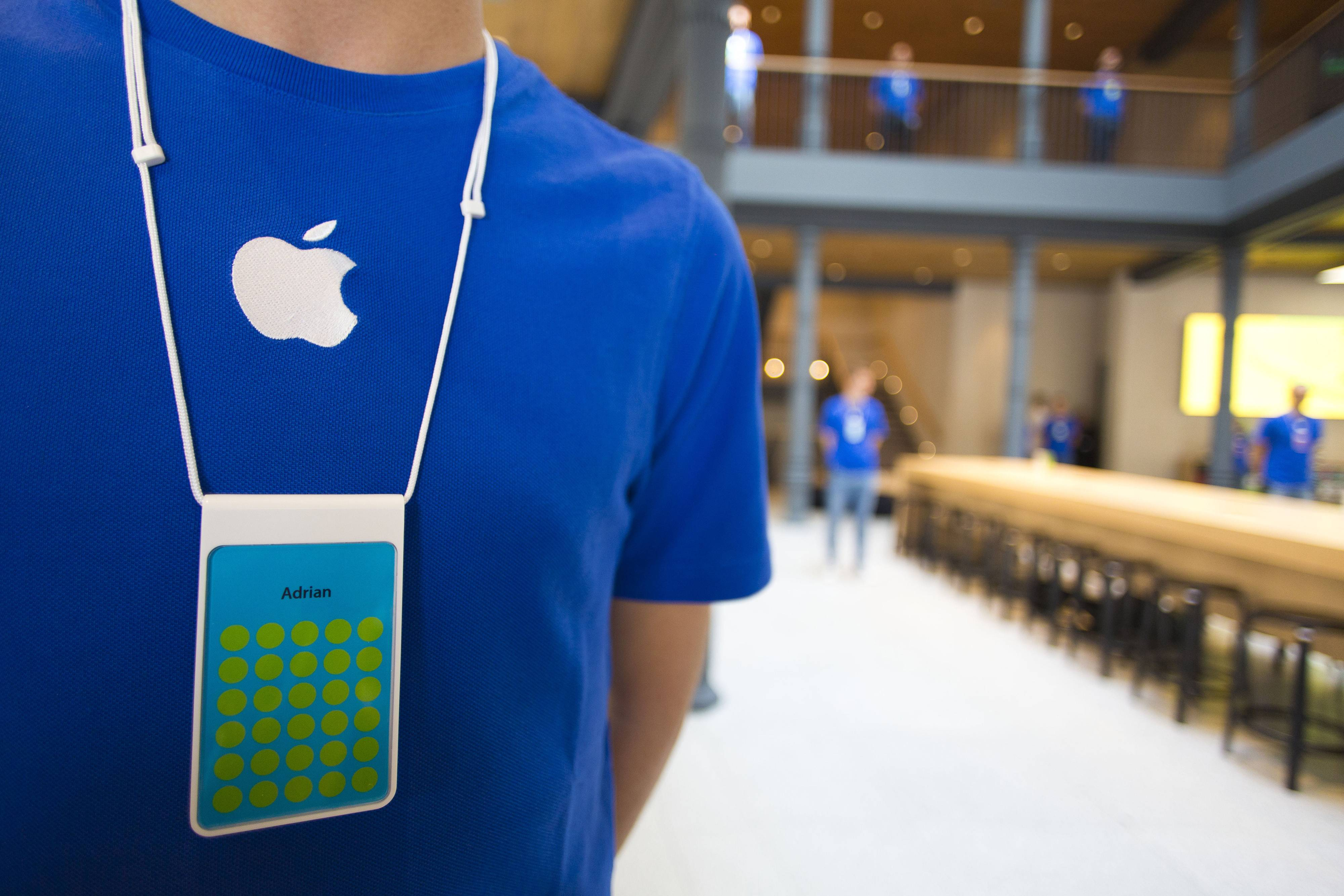 An employee wears a blue Apple-branded T-shirt and name badge during a media briefing at Apple Inc.'s new Spanish flagship store on Puera de Sol square the day before opening to the public in Madrid, Spain, on Friday, June 20, 2014. Apple Inc. introduced new health and connected-home features for the software powering the iPhone and iPad, laying the groundwork for a busy second half of the year as the company seeks to rev up its growth.