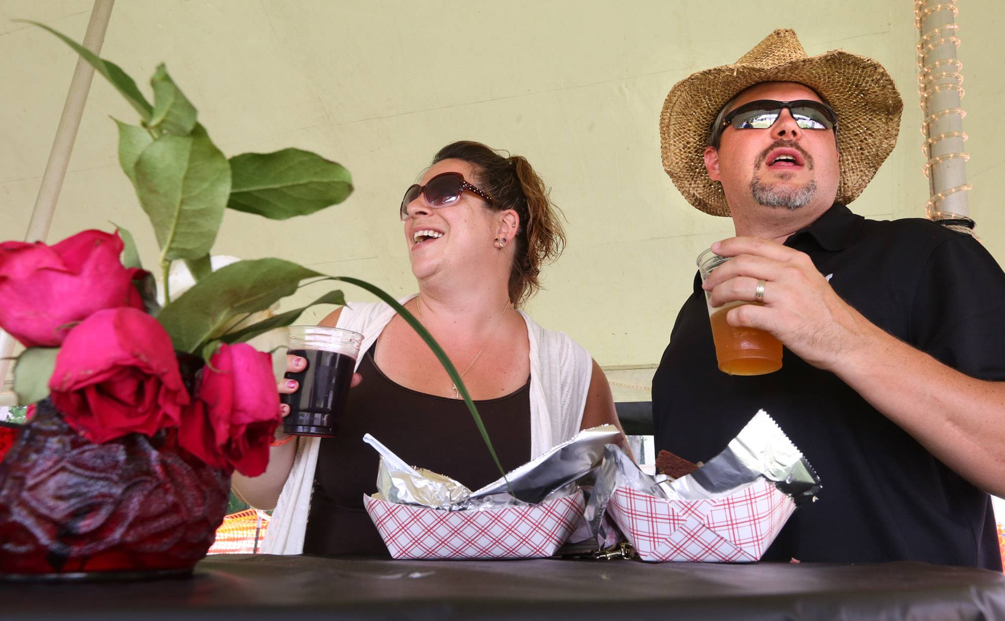 Kelly Englum of Elgin and her husband John, who works in Wauconda, enjoy the carnival and main stage from inside the Bliss Wine and Gifts of Wauconda wine tasting tent at Wauconda Fest while having a glass of sangria and a Phat Chance blonde ale during the festival's third day Saturday.