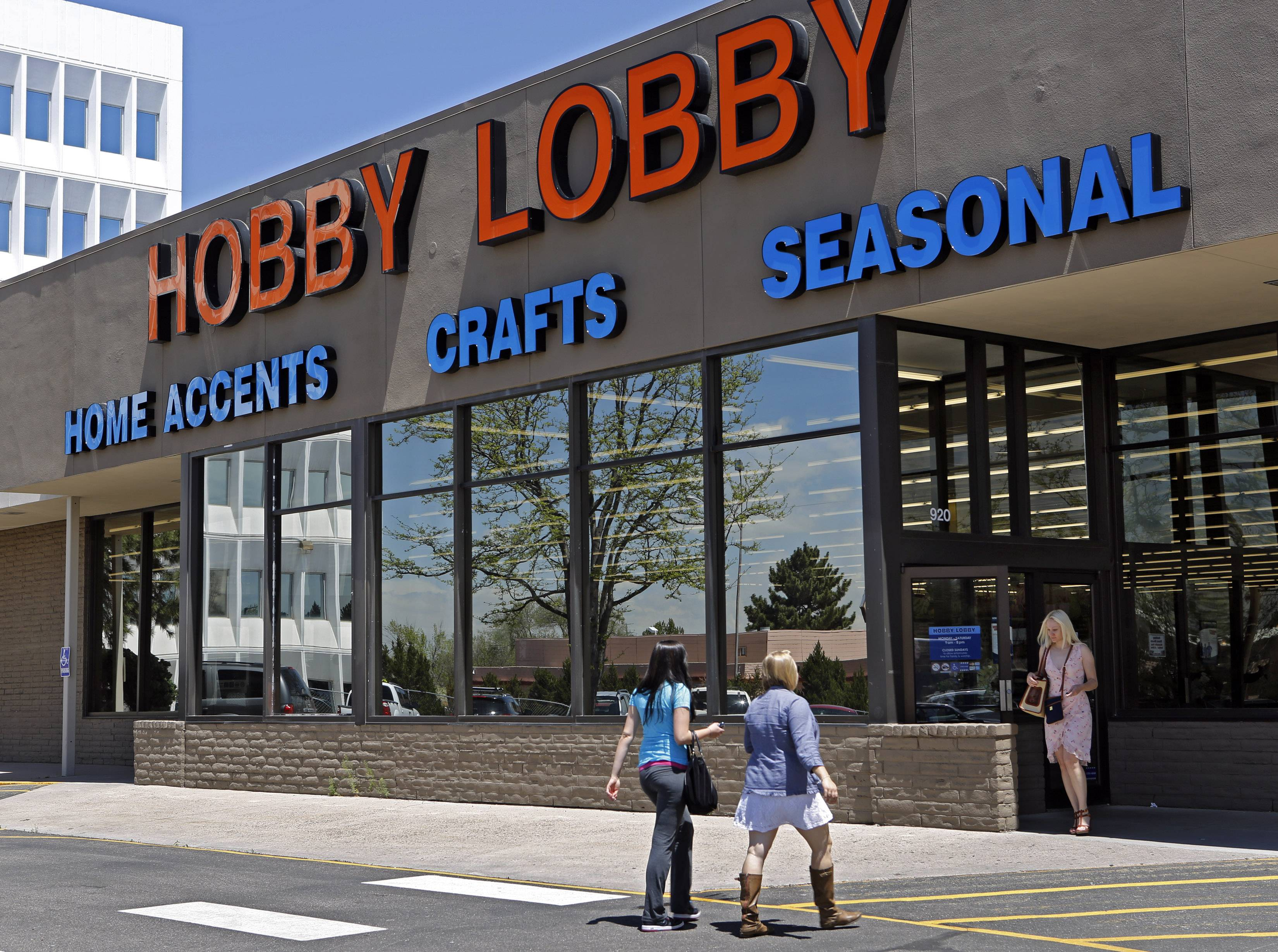 Customers enter and exit a Hobby Lobby store in Denver. The Supreme Court is poised to deliver its verdict in a case that weighs the religious rights of employers and the right of women to the birth control of their choice.