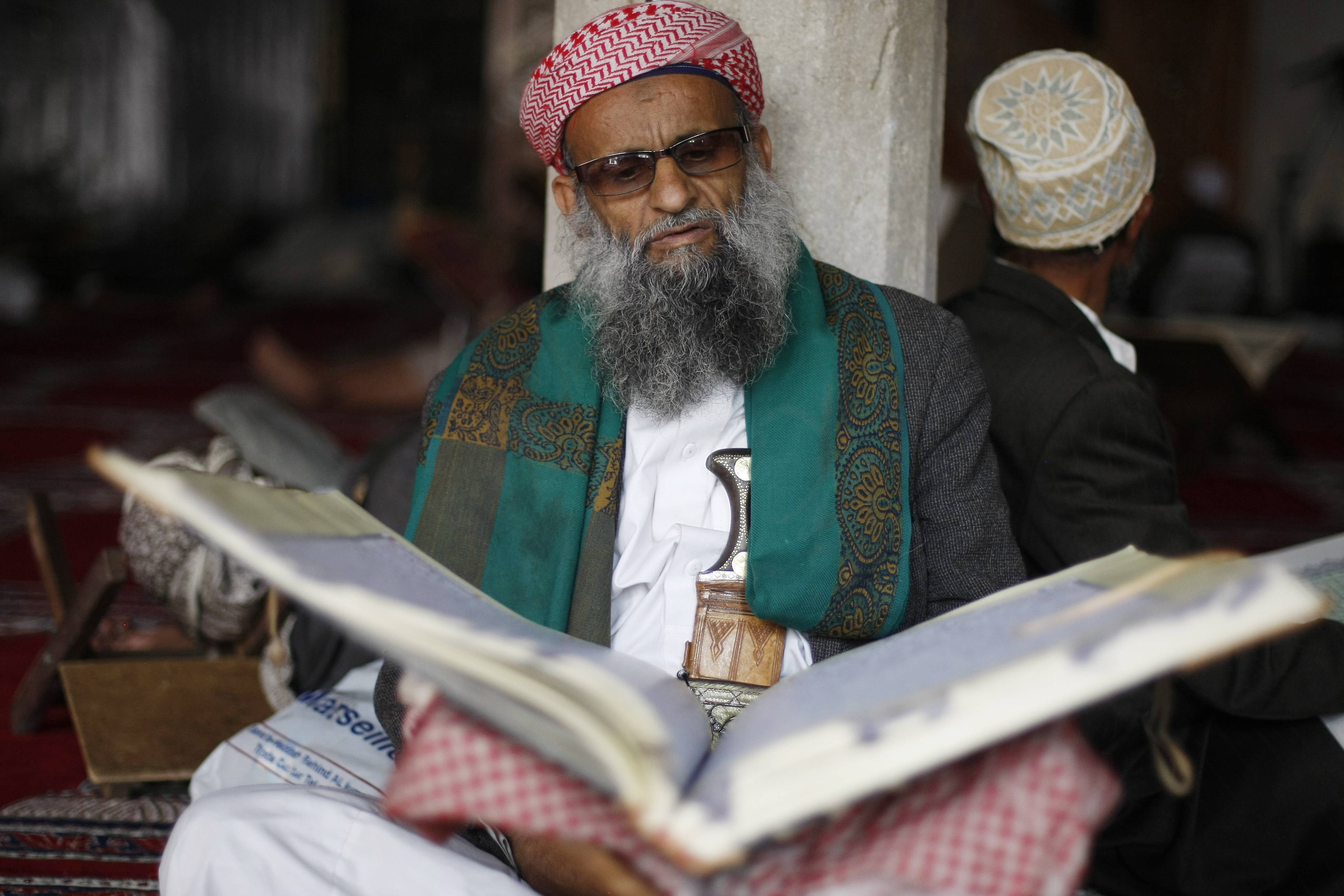 An elderly man reads verses of the Quran, Islam's holy book, on Saturday, the first day of the holy month of Ramadan, in the Grand Mosque in the Old City of Sanaa, Yemen.