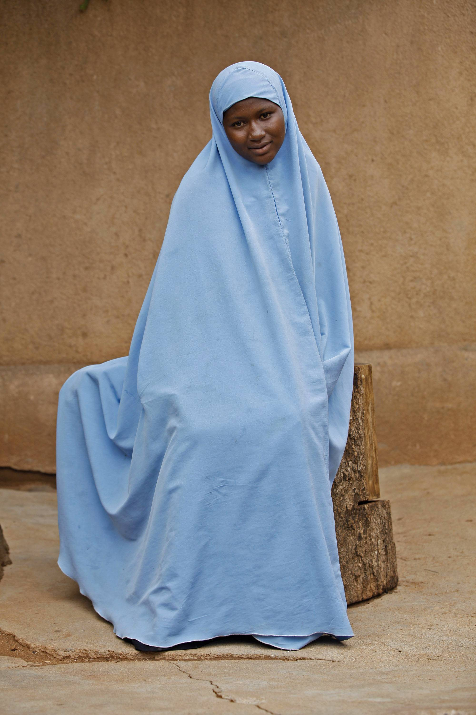 In this Sunday, June 1, photo, Maimuna Abdullahi sits outside her school in Kaduna, Nigeria. Maimuna wore the scars of an abused woman anywhere: A swollen face, a starved body, and, barely a year after her wedding, a divorce. But for Maimuna, it all happened by the time she was 14. Maimuna is one of thousands of divorced girls in Nigeria who were married as children and then got thrown out by their husbands or simply fled.