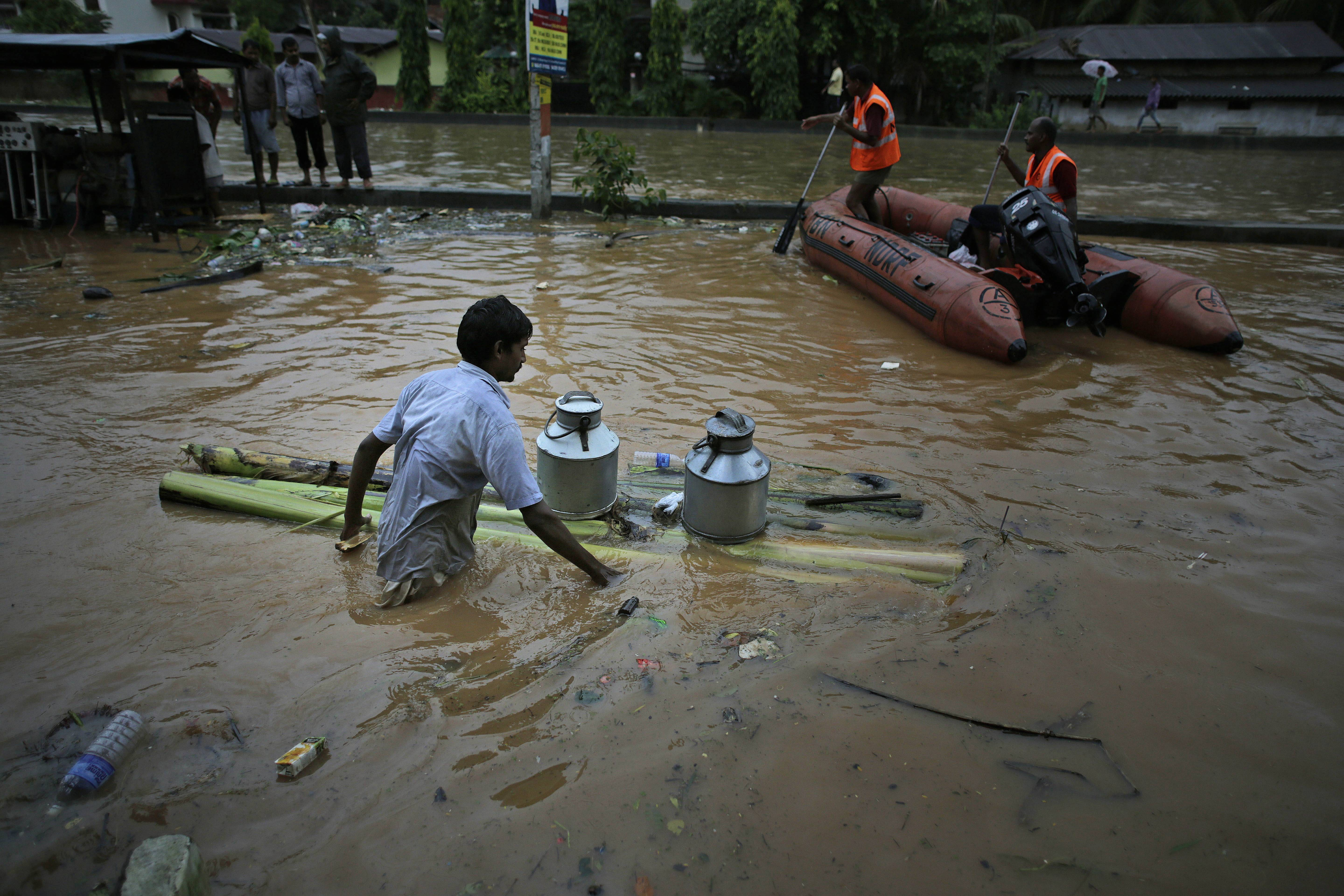 A flood affected man carries milk containers on a banana raft as members of India's National Disaster Response Force ride an inflatable boat to ferry flood to affected people in Gauhati, India, Friday, June 27. Several people were killed due to electrocution and landslides triggered by incessant rains in India's northeastern state of Assam, according to local reports.