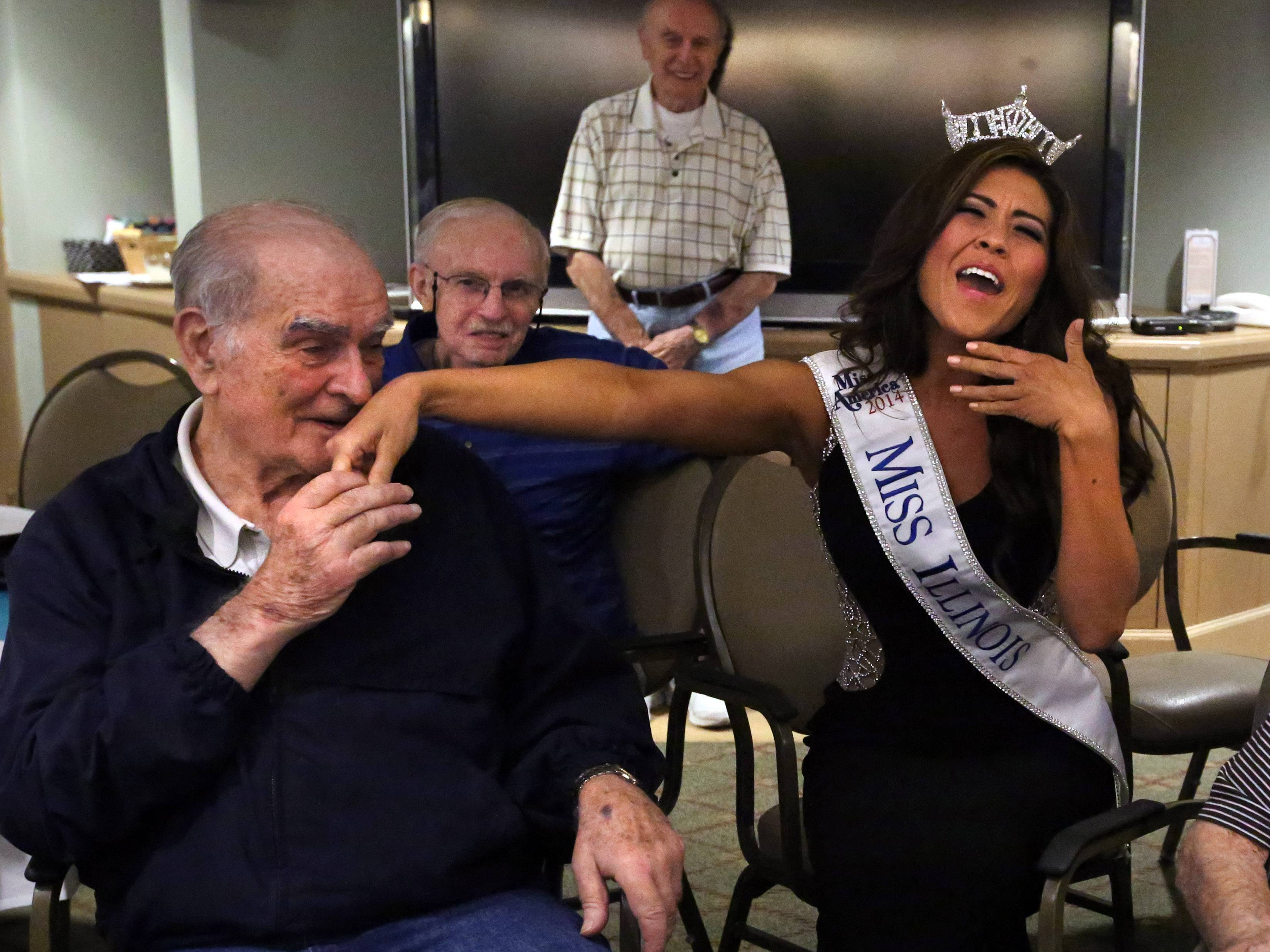 "Recently crowned Miss Illinois Marisa Buchheit reacts to a spontaneous kiss on the hand as she sings ""Il bacio"" (""The kiss"" in Italian) at Friday's Friends for Life happy hour at Brookdale Plaza senior living home, where Lewin is a resident, in Vernon Hills on Friday."