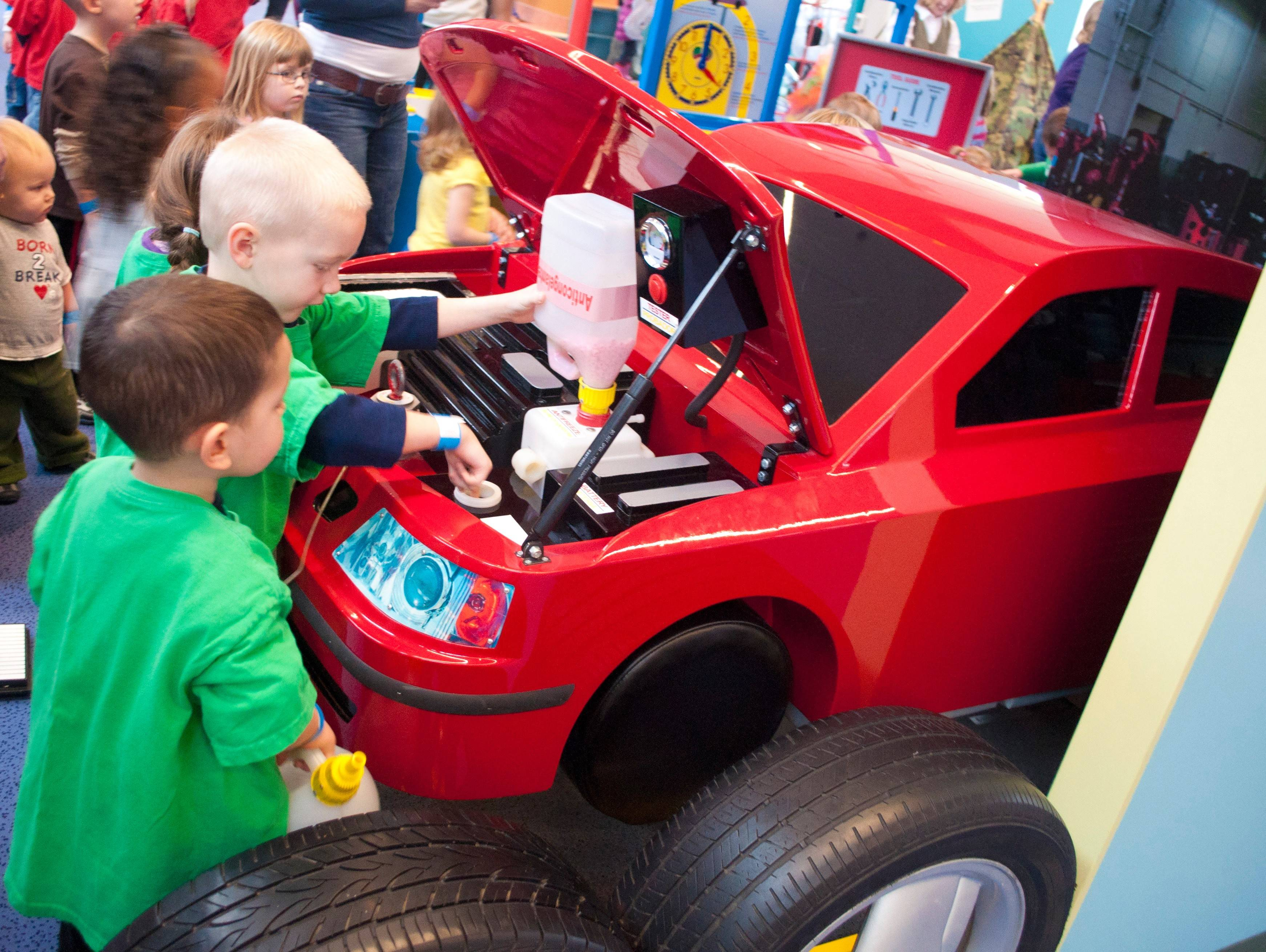 Children at the Kansas Children's Discovery Center work together to repair the car in the careers gallery.