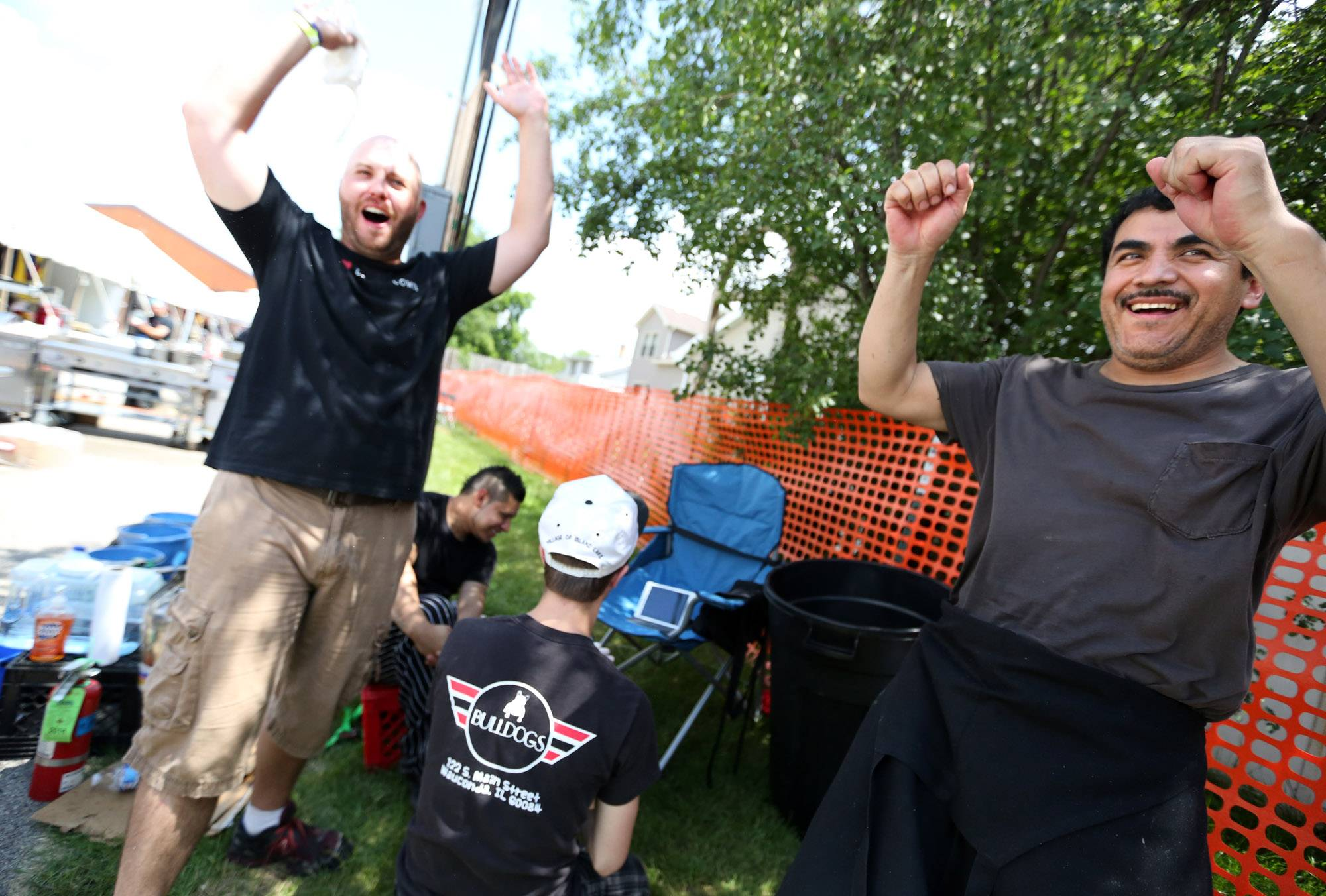 Patrick Ringel, manager of Bulldogs Grill, left, and chef Martin Velazquez celebrate a penalty kick goal by Chile against Brazil in the World Cup while watching the game on an iPad during a break behind their food stand at Wauconda Fest on Saturday.